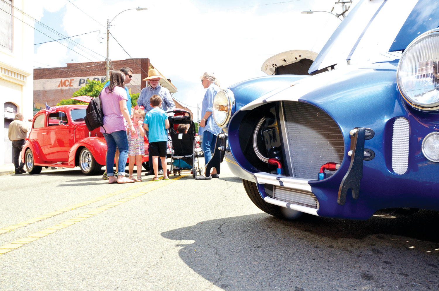 A Shelby Cobra, based on the Ford Mustang, sits at the curb while car fans pass by at Saturday's Spring  Chicken Festival.