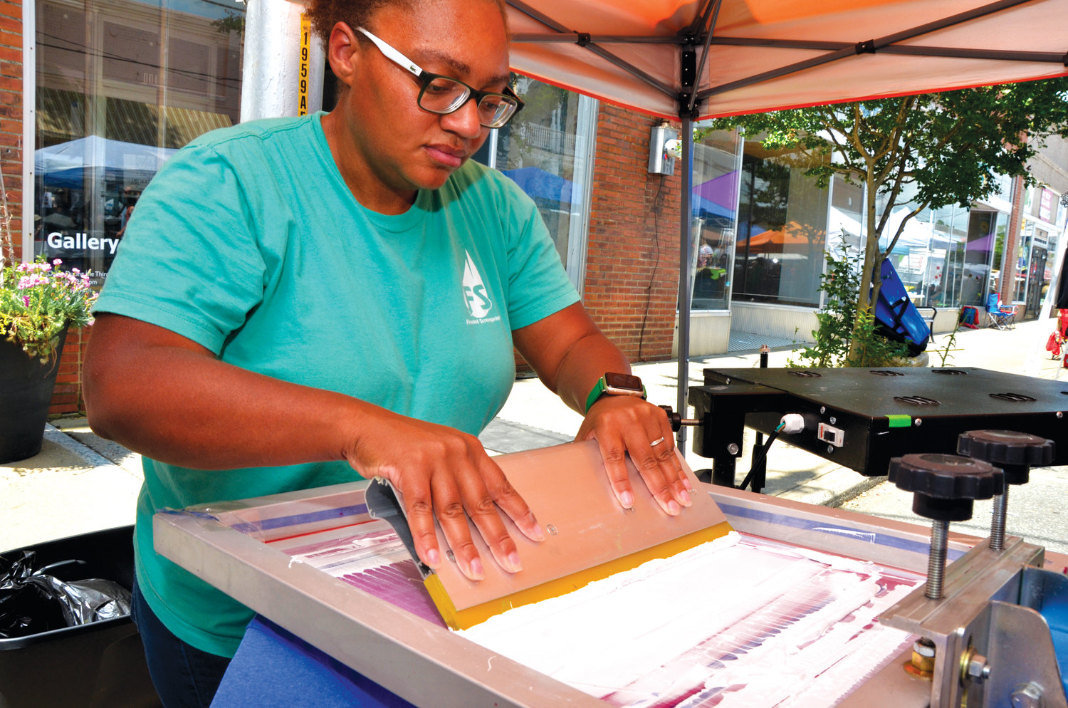 Keona Carr, with Flodded Screen Prints in Sanford, screen prints a T-shirt at the Spring Chicken Festival Saturday. The shirts could be printed, dried, and worn in just a few minutes.