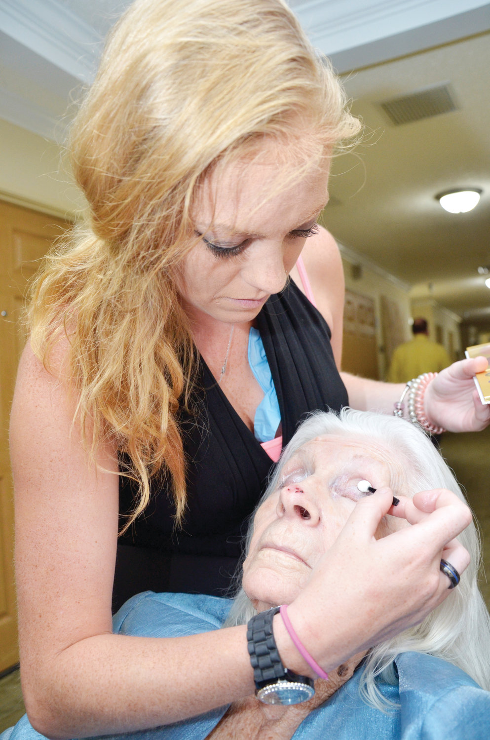 Caitlin Conn, a Certified Nursing Assistant at Cambridge Hills of PIttsboro, gives Louis Hope of Moody, Alabama a special touch of makeup before the start of the 2019 Ms. Cambridge Hills pageant. Conn said she enjoys hearing stories from fellow residents about where they're from, and special memories about their lives.