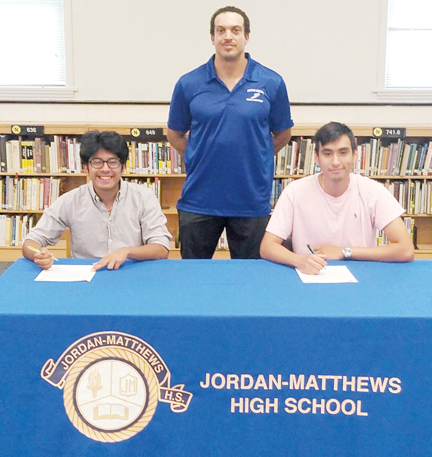 Eddy Girron and George Jucinto of Jordan-Matthews signed with CCCC to continue their cross country careers at the collegiate level. Eddy Girron (seated, left) and George Jucinto (seated, right) are shown signing with the Central Carolina Community College cross country program last week at J-M. Standing is CCCC Head Cross Country Coach Richard Briggs.