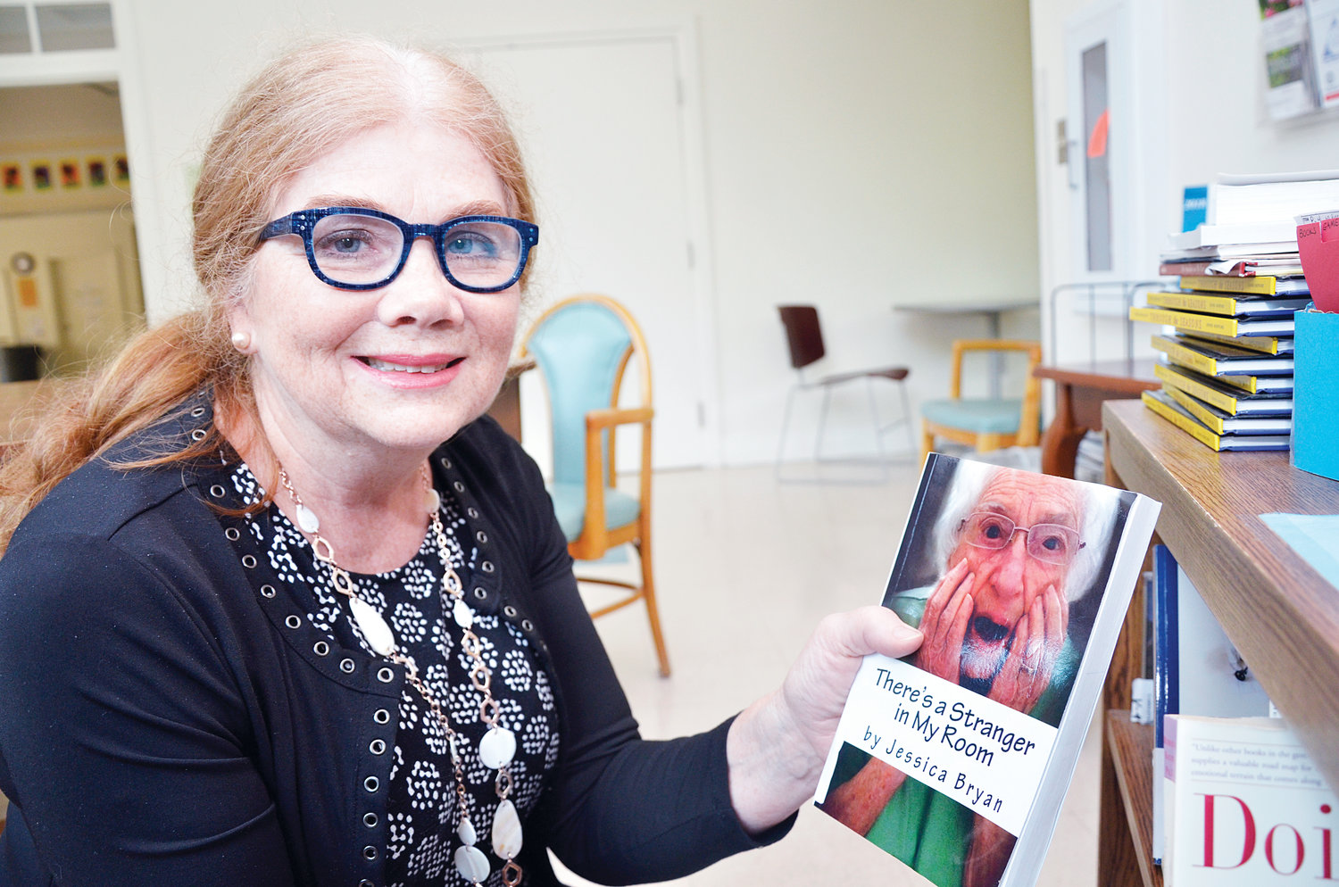 The Chatham Council on Aging's Susan Hardy shows a book written by Jessica Bryan detailing the experience, and sharing ideas, for a caregiver to a person with Alzheimer's.