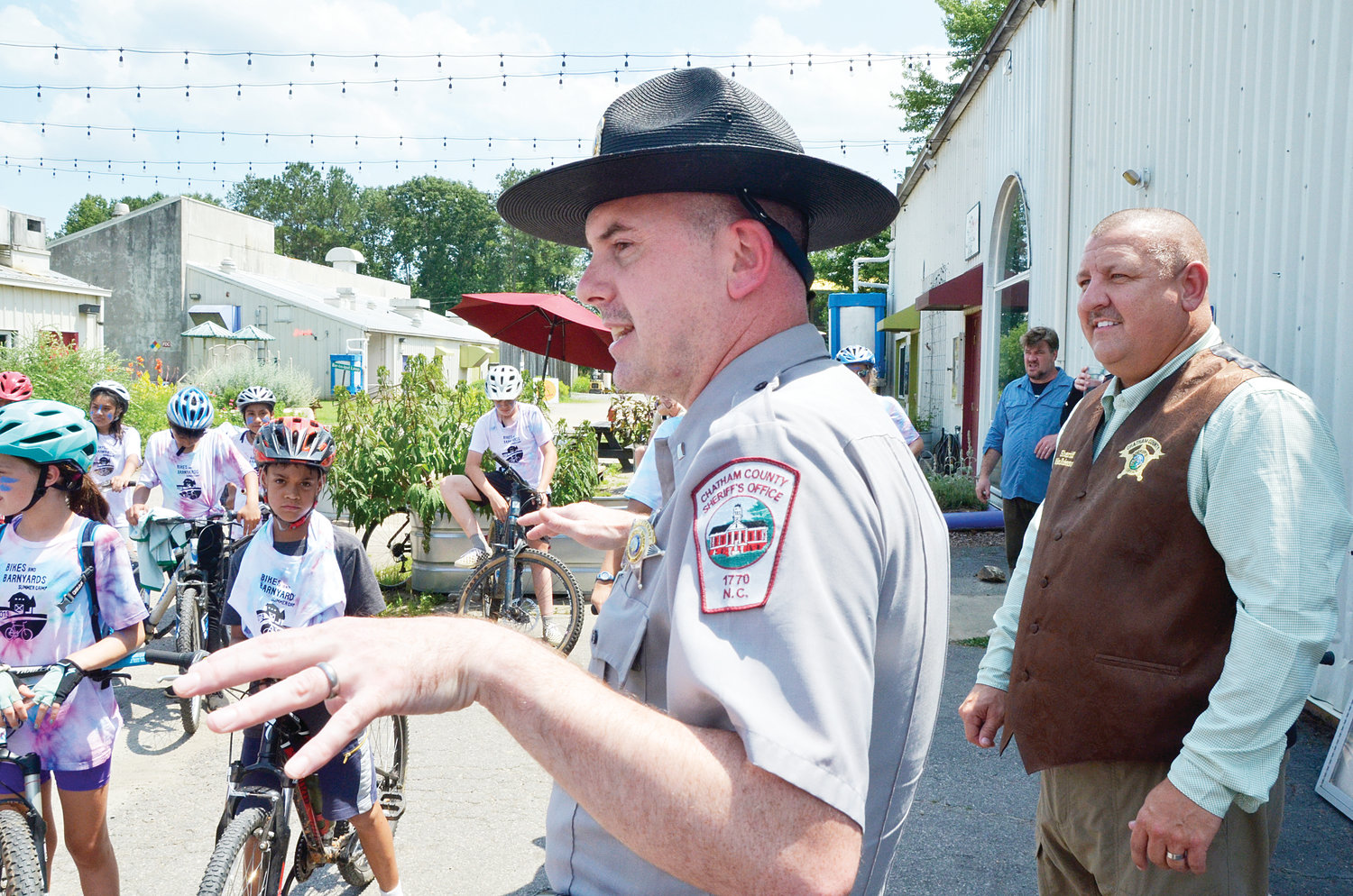 Chatham County Sheriff's Deputy Brandon Jones shares safety tips for the Bikes and Barnyards campers as Sheriff Mike Roberson, right, looks on. The bikers took a few minutes Thursday in the Chatham Beverage District courtyard to get final instructions before heading to Jordan Lake.