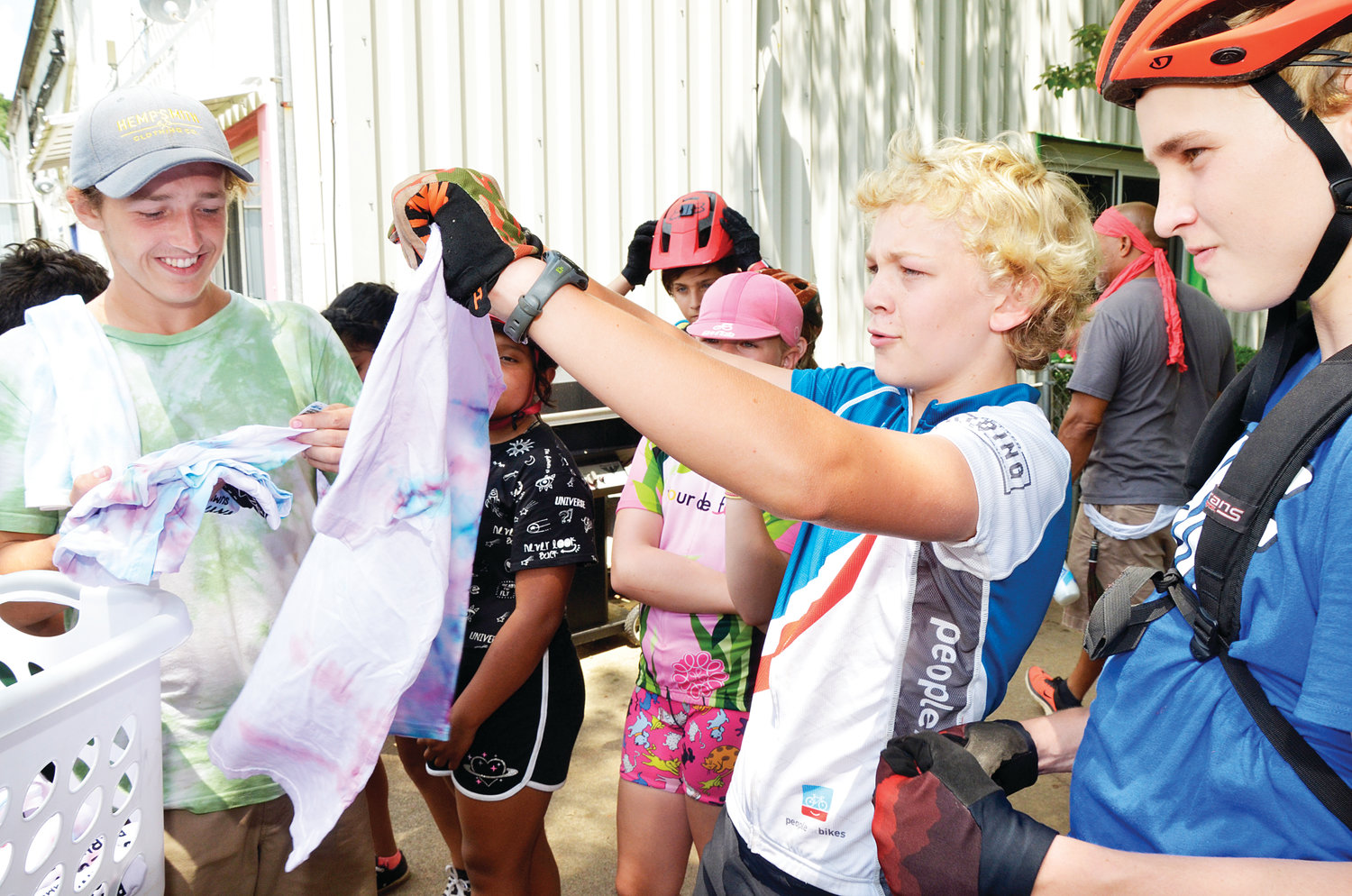 Asher Strauss holds out one of the t-shirts for the Bikes and Barnyards events given to the campers. The tie-dyed shirts were made by Arlo Estill, owner of Hempsmith, a Pittsboro hemp clothing company.