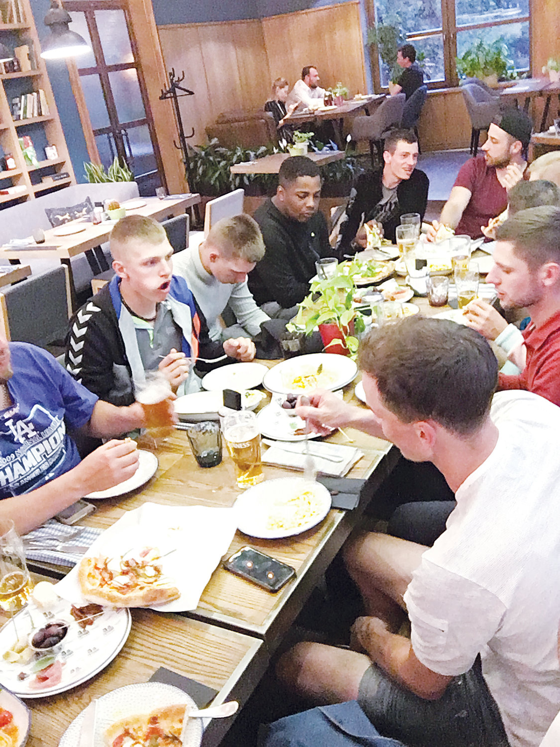 Breaking bread together. The Kaunas County baseball team from Lithuania enjoyed a lot of Russian cuisine as well as foods from other countries. Pittsboro native Woods Fines (head of the table) called his experience in Moscow incredible.