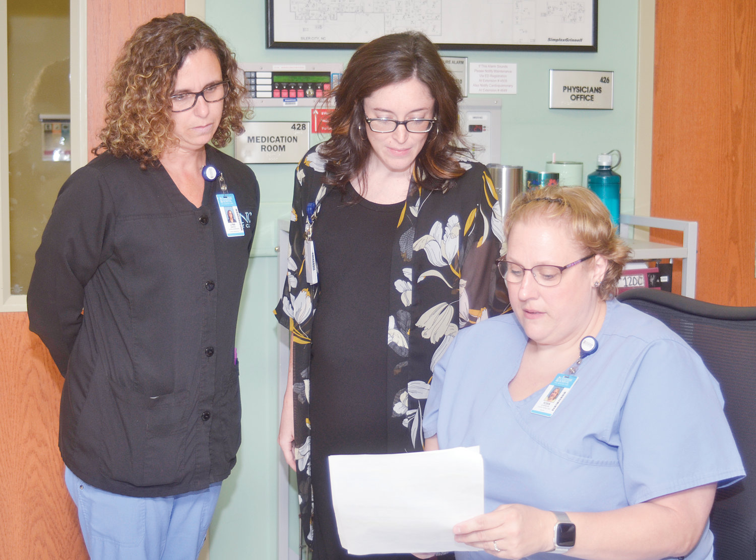 Lynn Emnons, Whitney Blalock and Robin Laverdure look over paperwork in the unit near Blalock's office at Chatham Hospital. Volunteers are needed in the offices to help with activities in the facility.