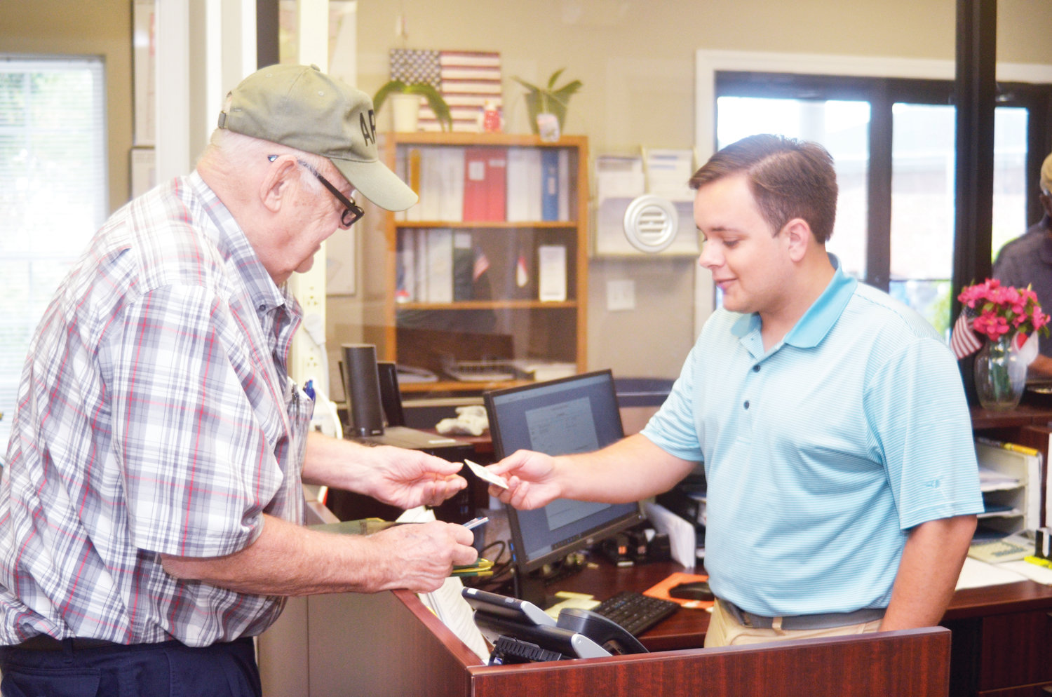 Siler City Mayor John Grimes (left) filed on Friday for re-election as the town's mayor. Chance Mashburn (right), elections specialist at the Chatham County Board of Elections, verified his identification upon filing.