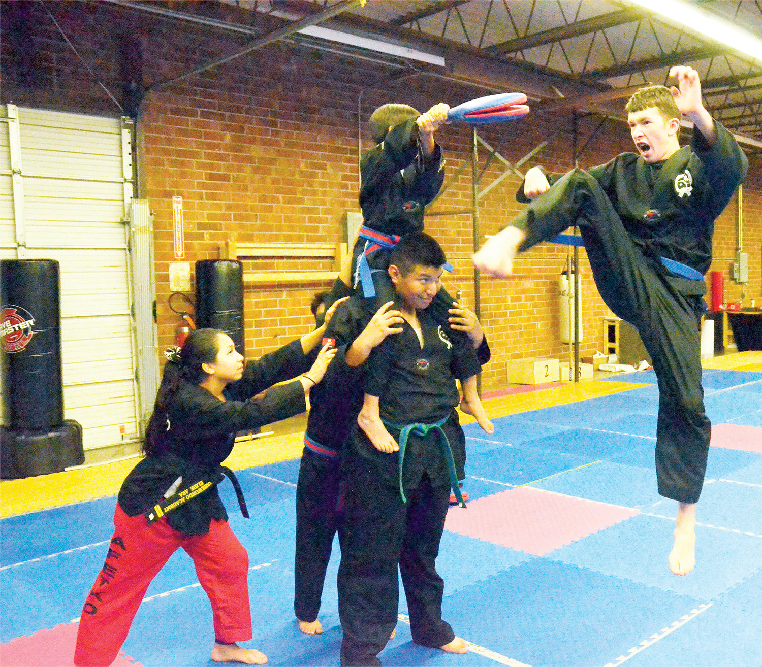 Logan Sammons, 14, delivers a snap kick during practice at the AFE TKD Martial Arts The Best of Siler City Academy.