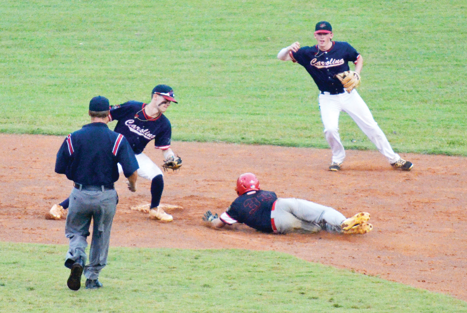 Carolina Coyote's Tyler Myers reaches to tag out Deep River Muddog Noah Handy as he slides into second Tuesday, July 16 at Craven Stadium in Ramseur. Handy was called out as another Coyote player watched, but the Muddogs won the contest, 2-1.