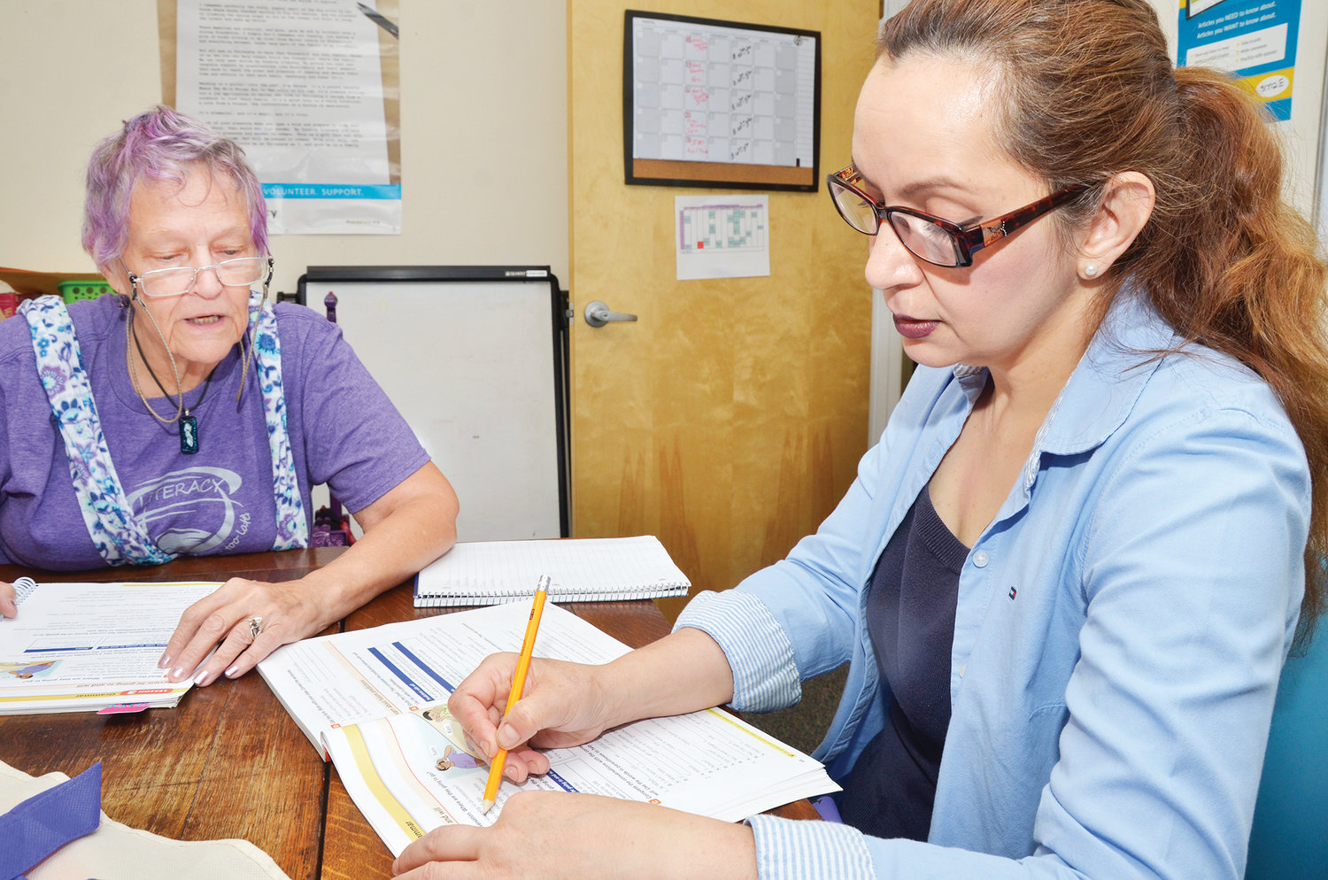 B Demers, left, gives Aidee Orozco a lesson in the English language at the offices of the Chatham Literacy Council. Demers speaks English and Spanish, and helps her students with the difficulties acquiring the unfamiliar words.