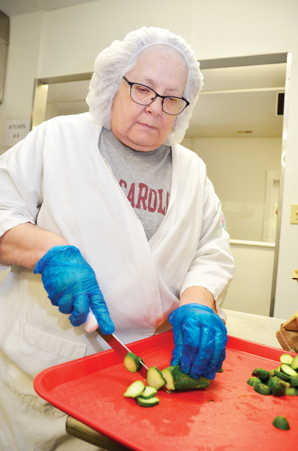 Sandy Brown, co-owner of Sandy & Co., slices pickles for the many varieties offered by her company in the showroom. Southern Supreme sells pickles, jellies, chocolates and other products when fruitcakes are not in demand.