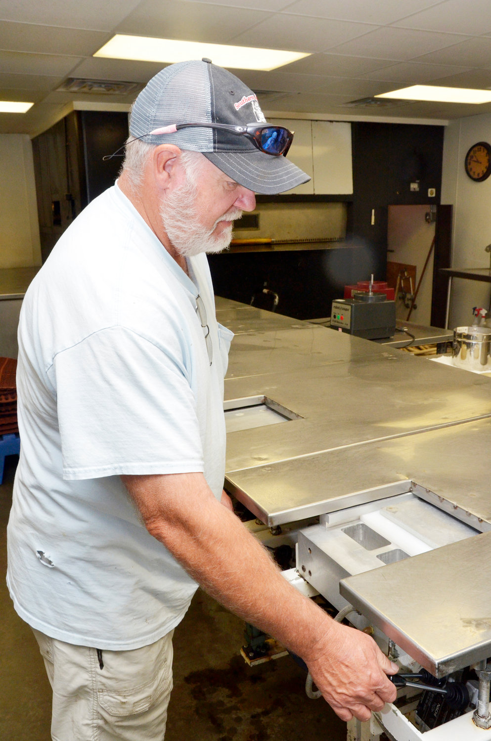 After cakes are baked in the oven, they are packaged while still pliable into forms to create the individual loaves. Randy Scott, co-owner of Sandy & Co., demonstrates with a machine that he built for the purpose.