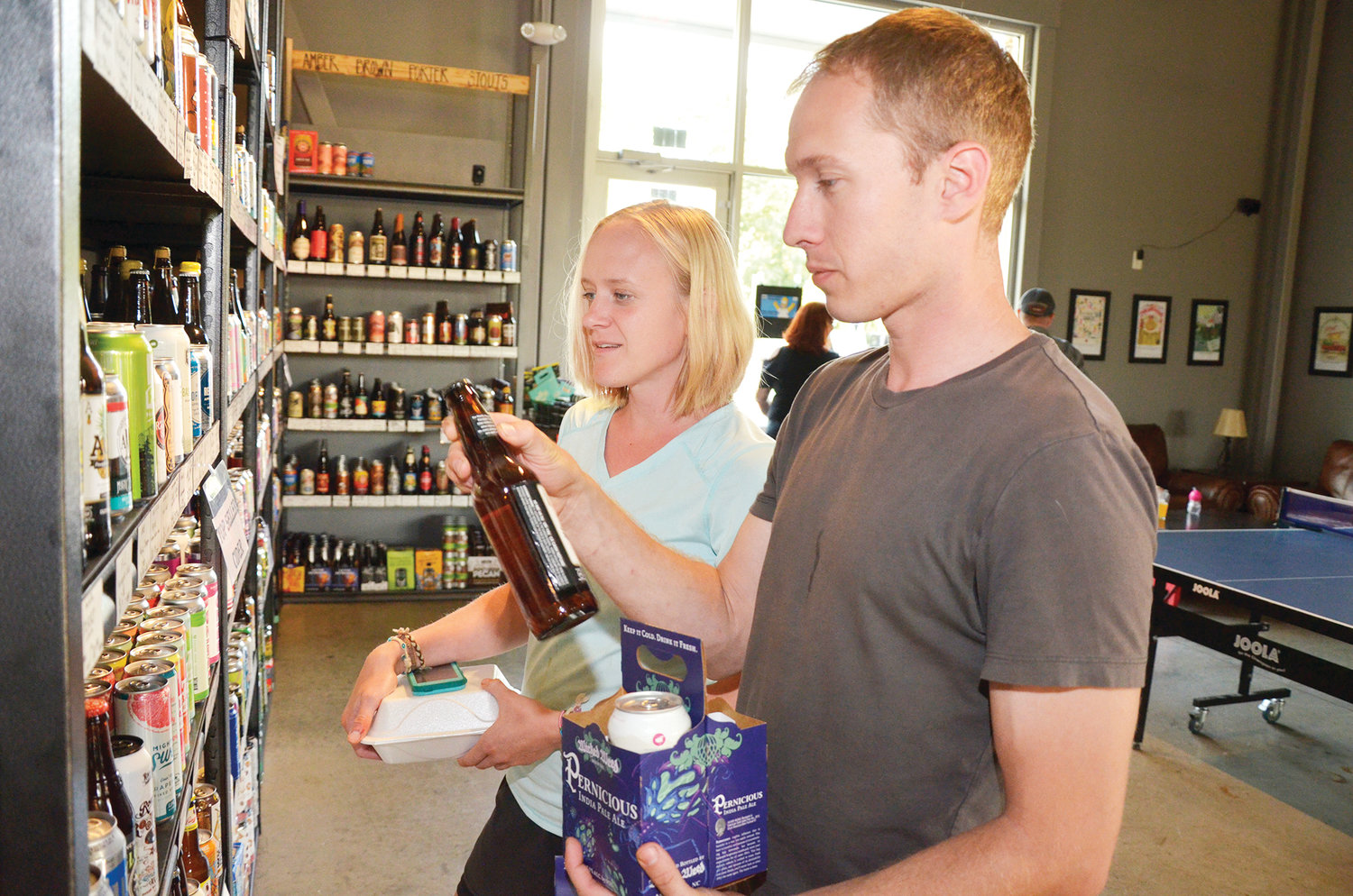 Sam Polak, left, assists Scott Heffley as they pick out a custom four-pack of beers from the selection on the wall. The two were picking up beers for a concert supply for the weekend.