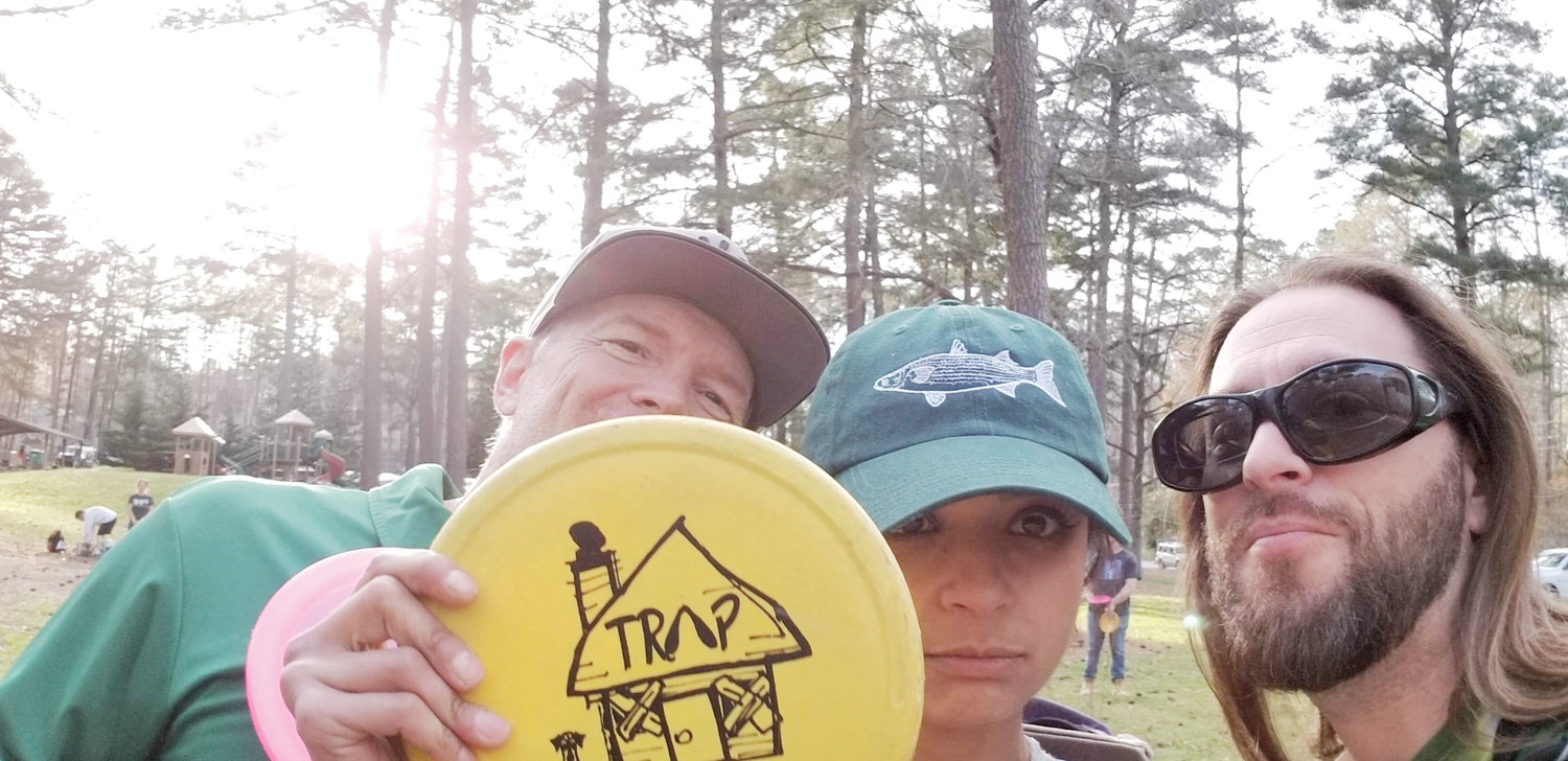 Disc golf is about the friendships you build as well as the game. Clay, Zee, and Detroit Drew show off a disc she won as a CTP.