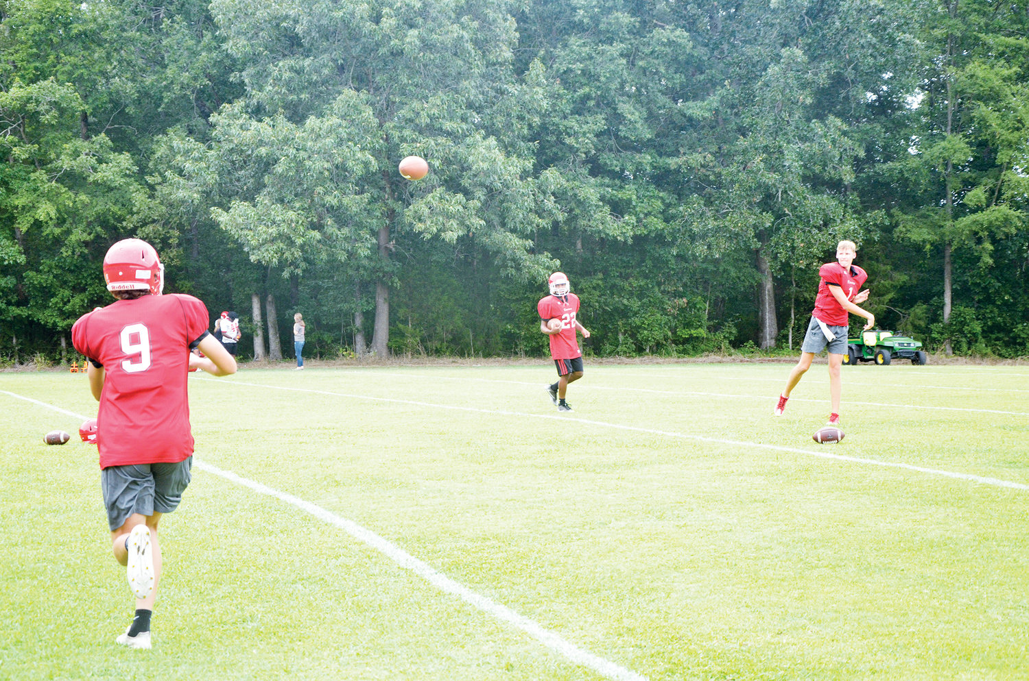 Chatham Central's Micah Gurley catches a pass from Michael Moore Monday afternoon at a pre-season practice for the Bears while Malachi Moore, center, watches on. Chatham Central kicks off its 2019 campaign August 23 against Eastern Randolph.