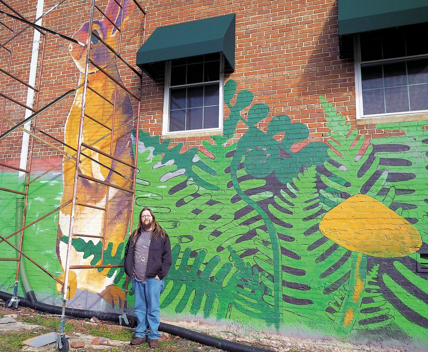 JR Butler stands in front of the new mural on the back of the Chatham Lofts that he installed.