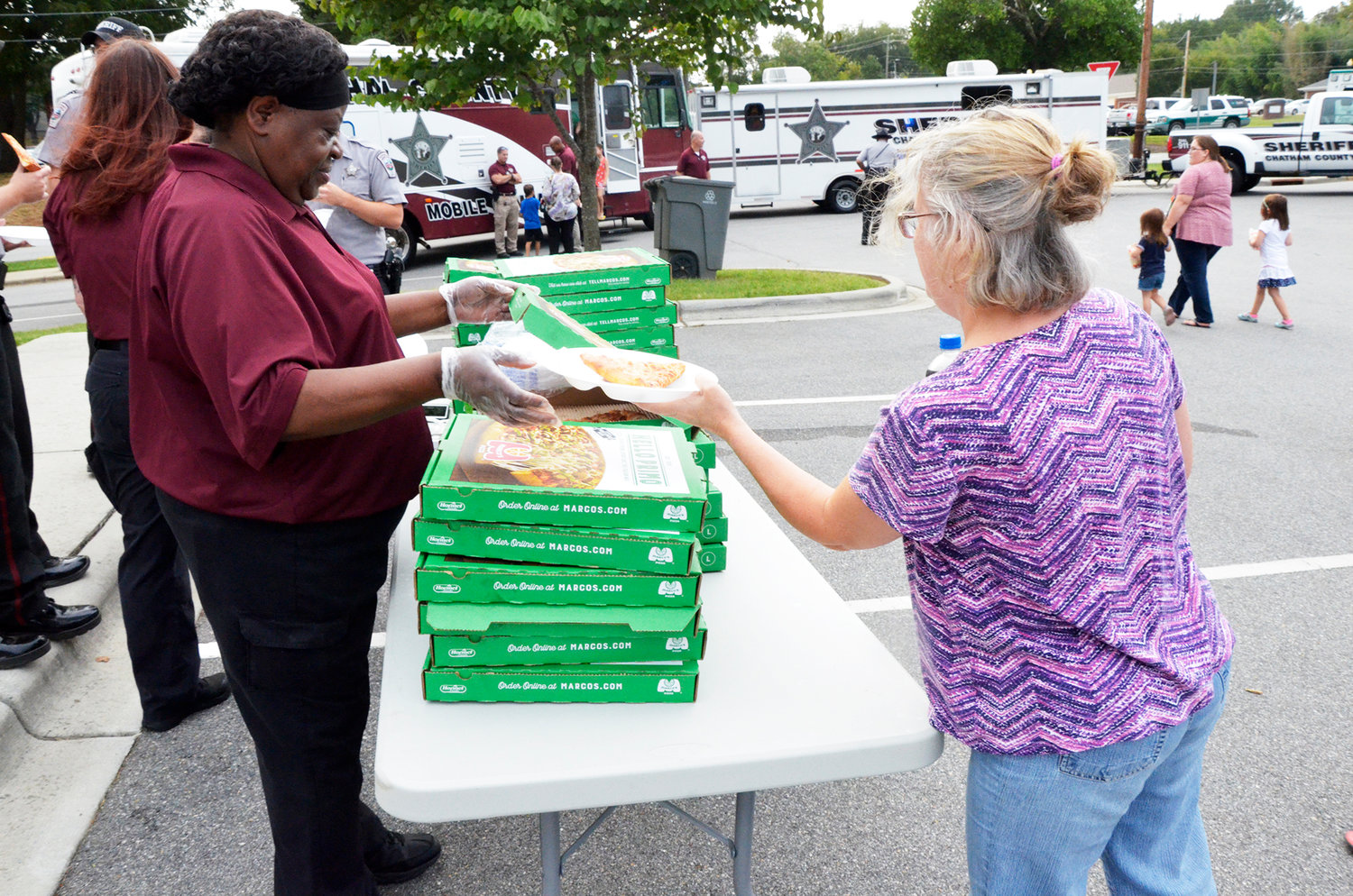 Lisa Gaines snags some hot cheese pizza from deputies at the Chatham County Sheriff's Office Community Appreciation event last Friday. The event offered the public a chance to meet the deputies, see their mobile command units and other law enforcement tools.