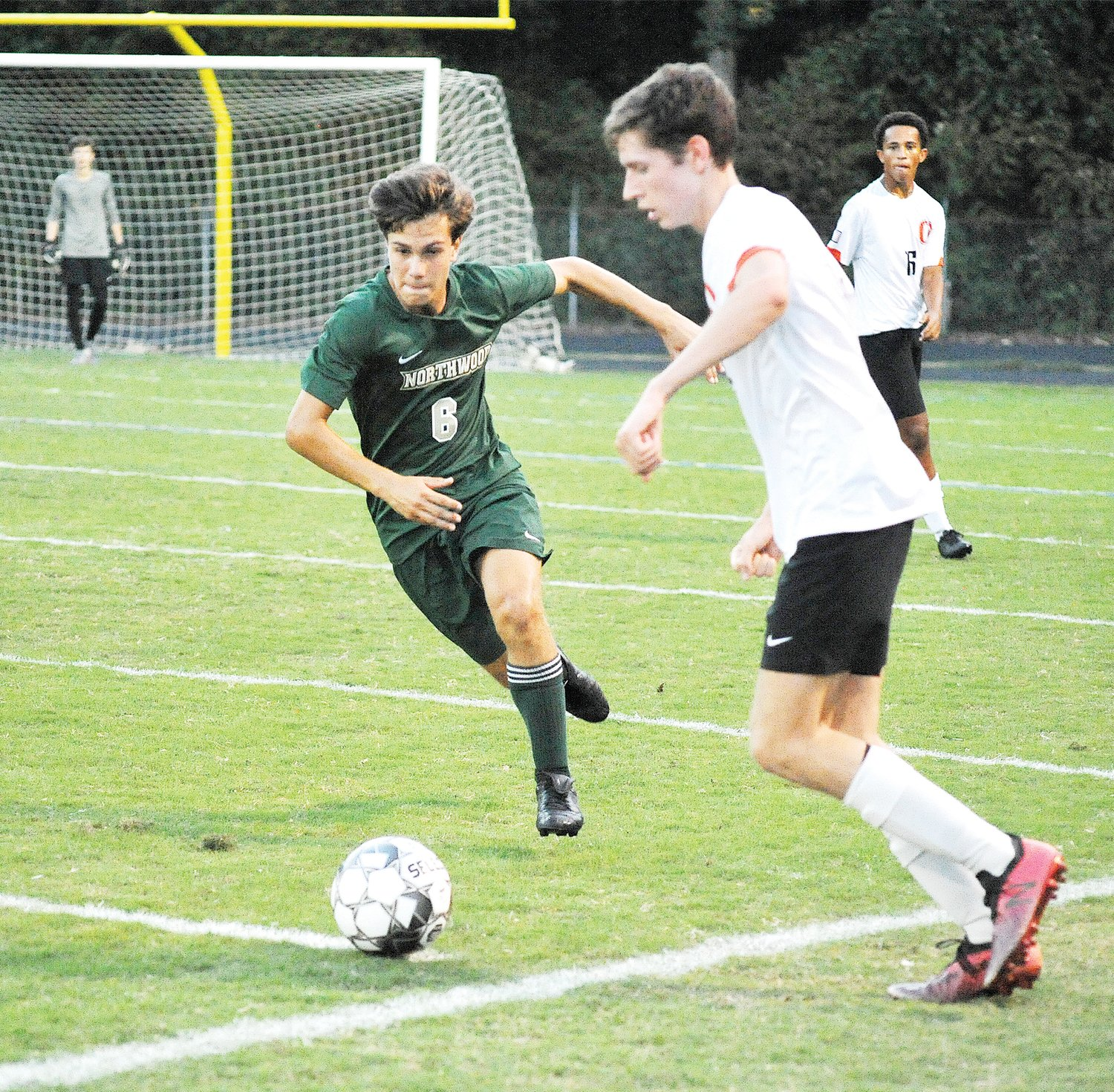 Determination!.Northwoods' Gino Valenti takes the ball past Orange Highs' Luke Phillips in their Sept. 23rd game as Kobe Thompson watches. The home field advantage added to the score with Northwood victorious in the match, 2-1.