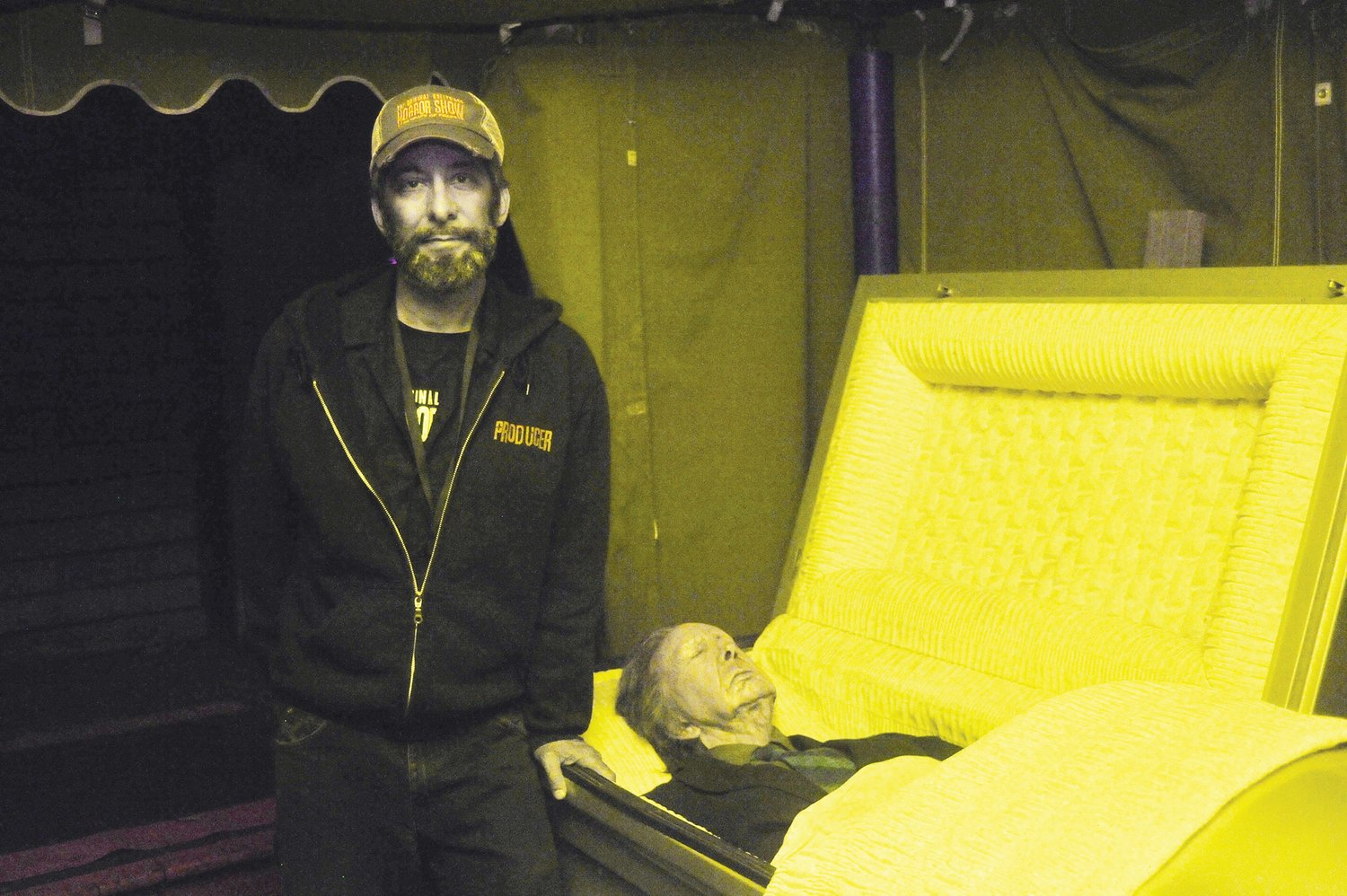 Professional movie make-up artist Starr Jones, co-creator of The Original Hollywood Horror Show in Snow Camp, stands next to a coffin whose occupant (a prop) wears the last life mask of the late actor Vincent Price.