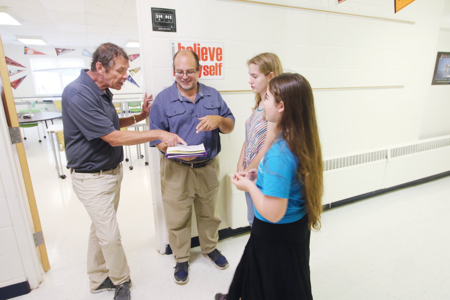 Chatham School of Science & Engineering student Lily Taylor (second from right) and her sister, Miana, look on while Science & Engineering educator Patrick Tillett speaks with their father, Mark, during open house on campus Aug. 6.