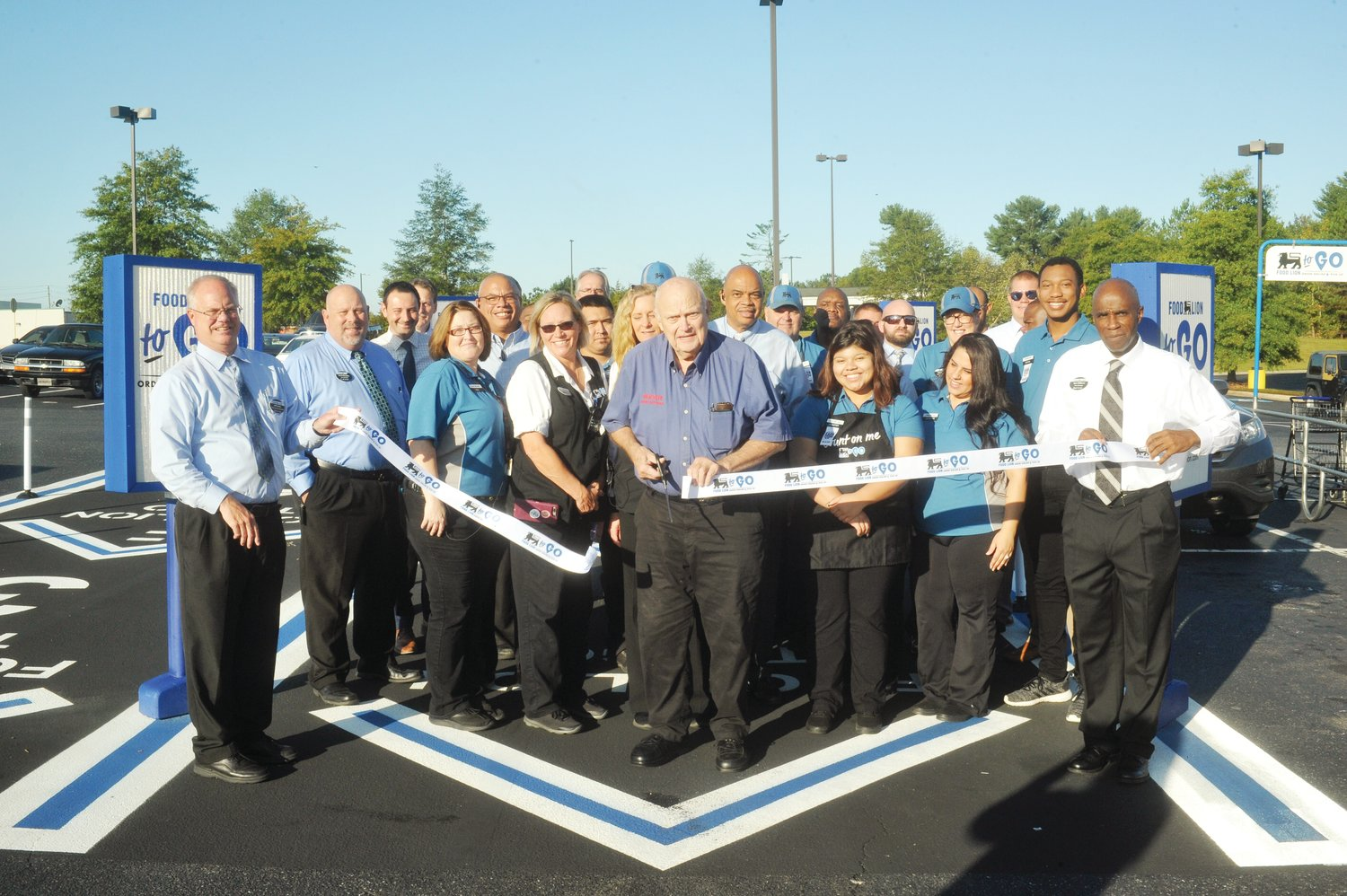 Mayor John Grimes, flanked by members of Food Lion management and employees, cuts the ribbon on the new Food Lion To Go program at the Siler City Food Lion last Monday morning. The new concept in the local store offers online shopping with delivery to the customers car for a low fee. The To Go program is now in operation.