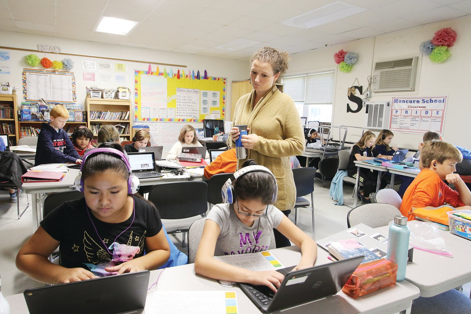 Moncure School educator Alicia Shoup looks in on 5th-grader Angie Rueda Perez (left) and 6th-grader Citlaly Perez.