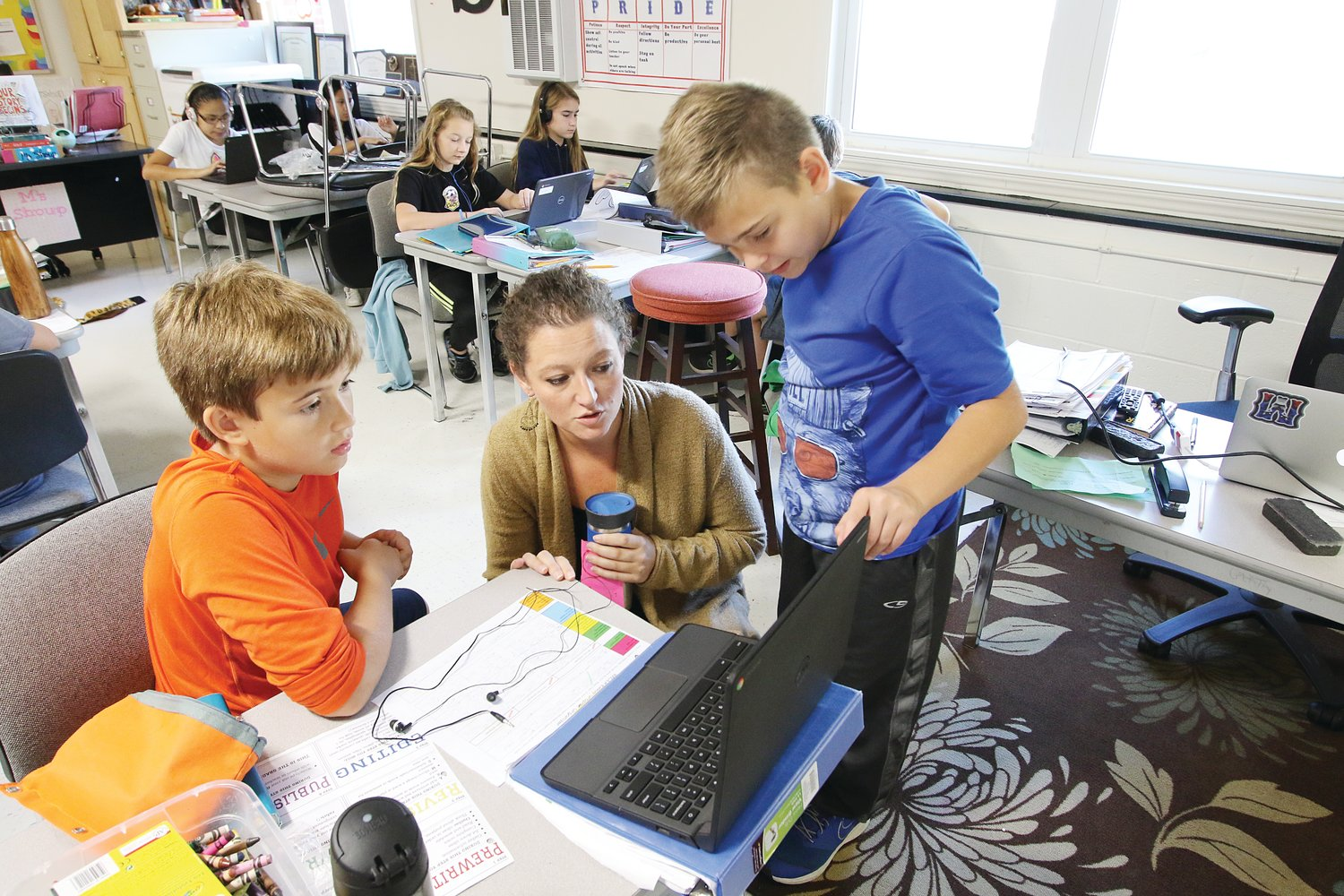 Moncure School's Alicia Shoup works with 5th-graders Lucas Ferri (left) and Gunnar Goodwin.