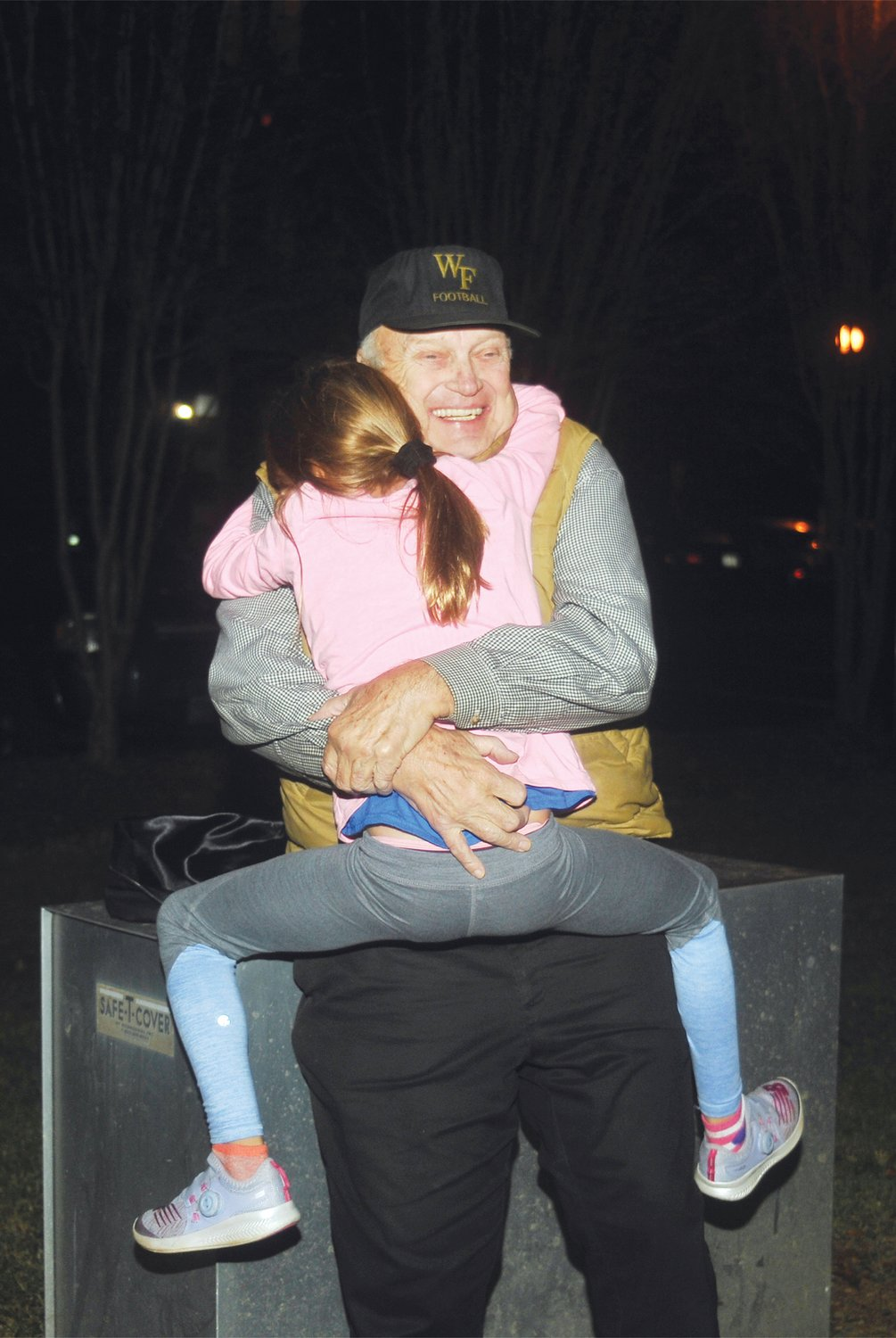 Siler City Mayor John Grimes gets a big hug from his granddaughter Sophia Grimes Tuesday night after learning of his re-election..