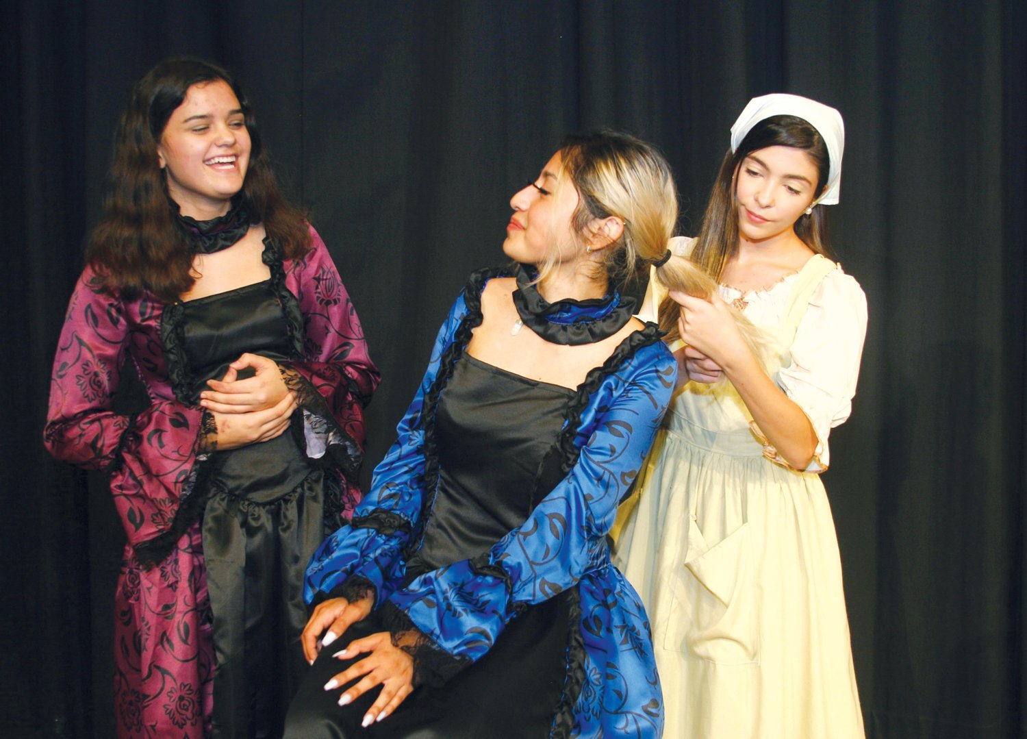 Cinderella (Kayli McIntosh at right) helps her stepsisters Florinda (Shelia Hernandez, seated) and Lucinda (Alana May) get ready for the King's Festival.