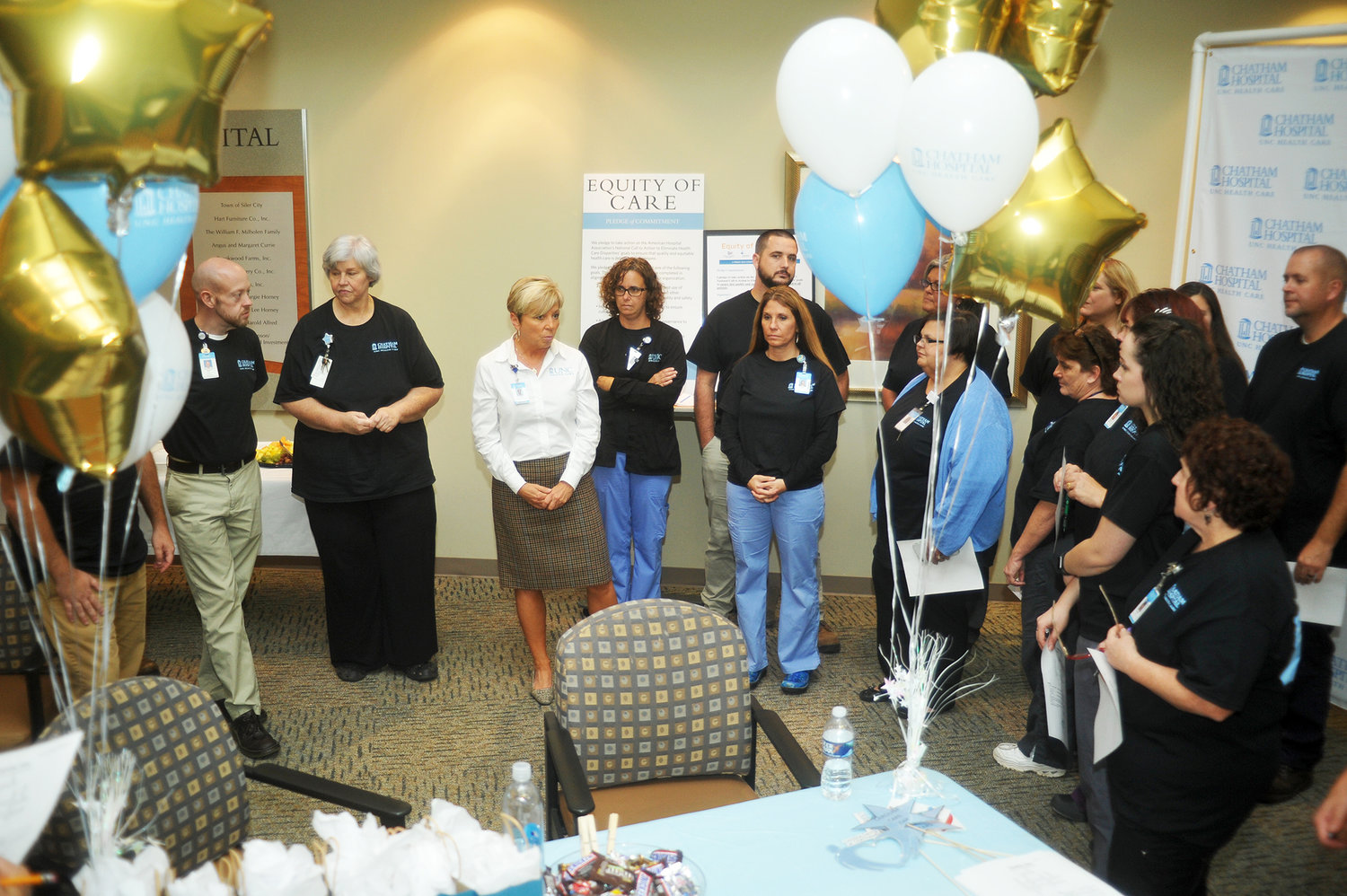 Re-Affirmation.Tammy Needham, in white, speaks to the assembled caregivers at Chatham Hospital about the Carolina Care program. The event, Oct. 22, was a program to re-affirm the commitment of the hospital to the guide's specific steps to quality care for their patients.