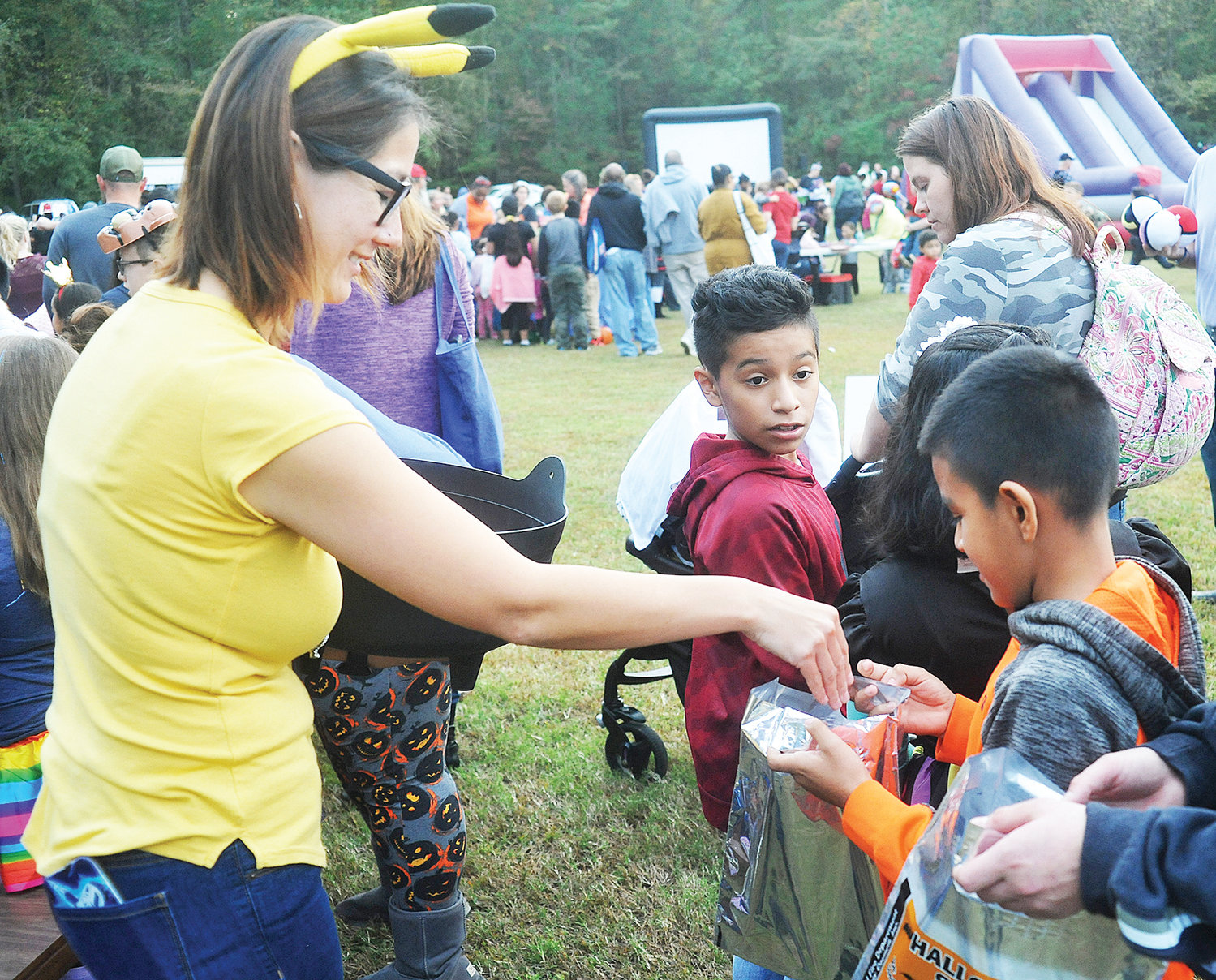 Mary Earle, from the Wren Library in Siler City, gives candy to Hamilton Garcia last Friday. Garcia was one of the large group of children and families that came through Bray Park for the third annual Fall-O-Ween event.