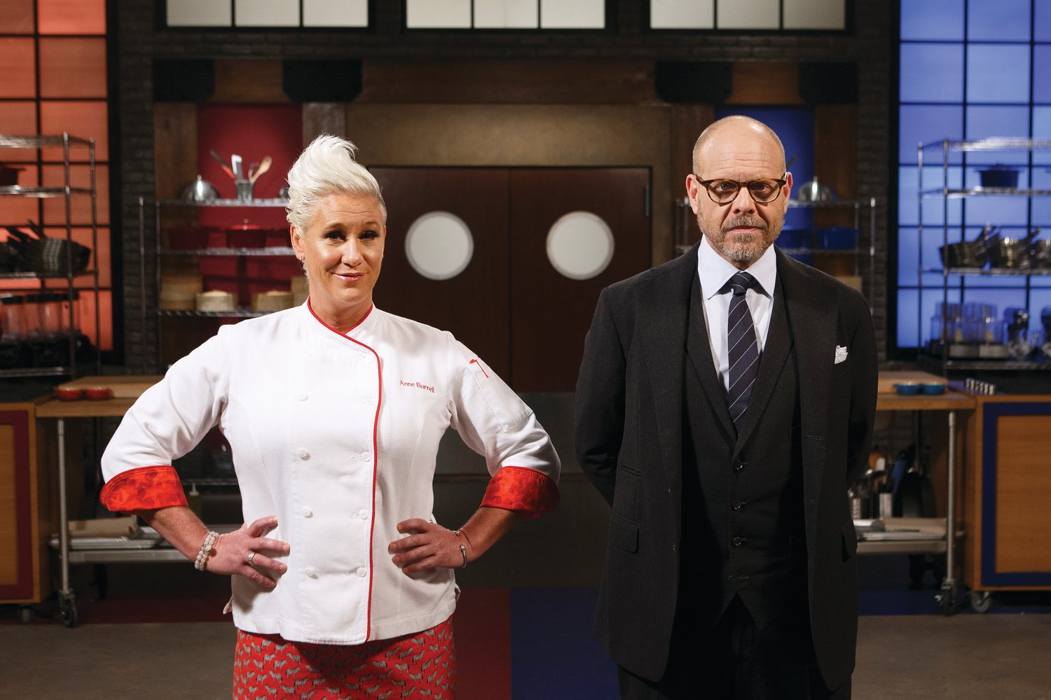 Chef hosts Anne Burrell and Alton Brown pose together, as seen on Worst Cooks in America, Season 18.
