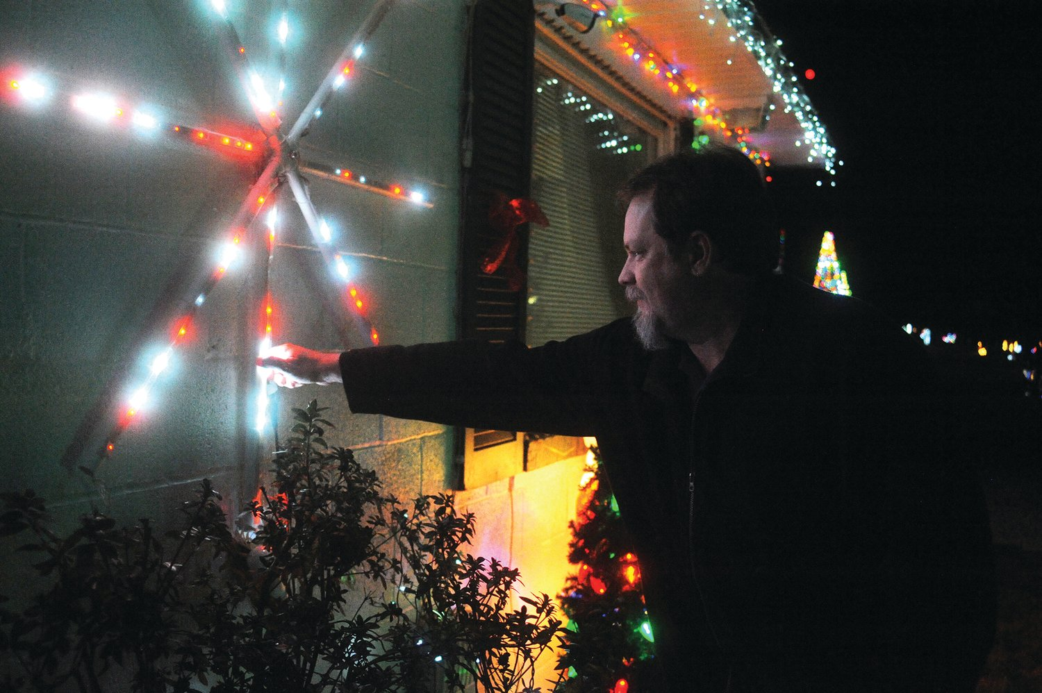 Scott Mace works in the information technology field and uses his knowledge to control the lighting display used at his residence each Christmas season. This lighting star was out of adjustment, and required a nudge to correct the problem.