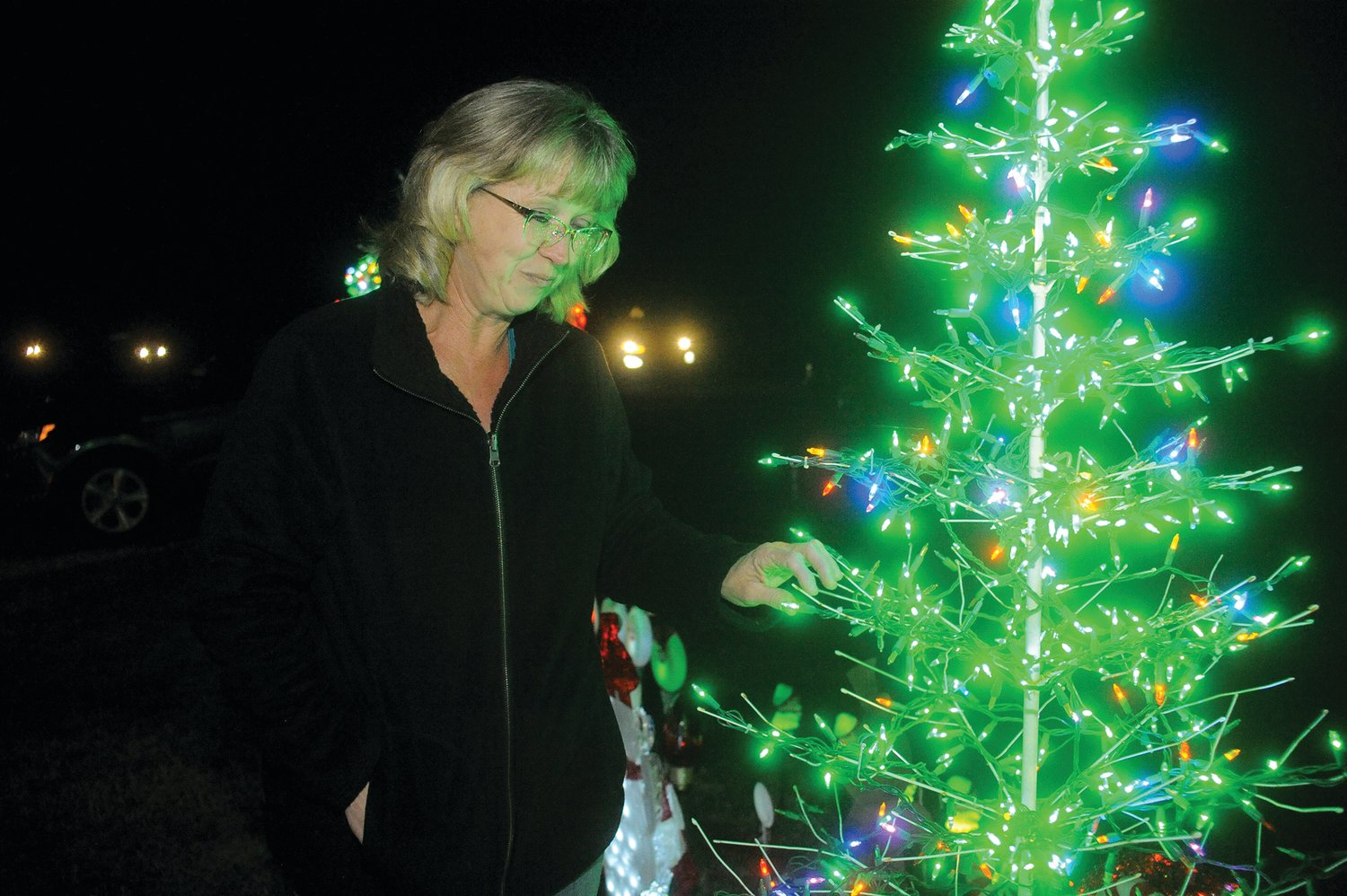 Michelle Mace checks and adjusts the lights on one of many trees decorated at her home for the Christmas season. Maintaining the display is one of the many tasks involved in keeping the holiday lights bright and cheery through the season.