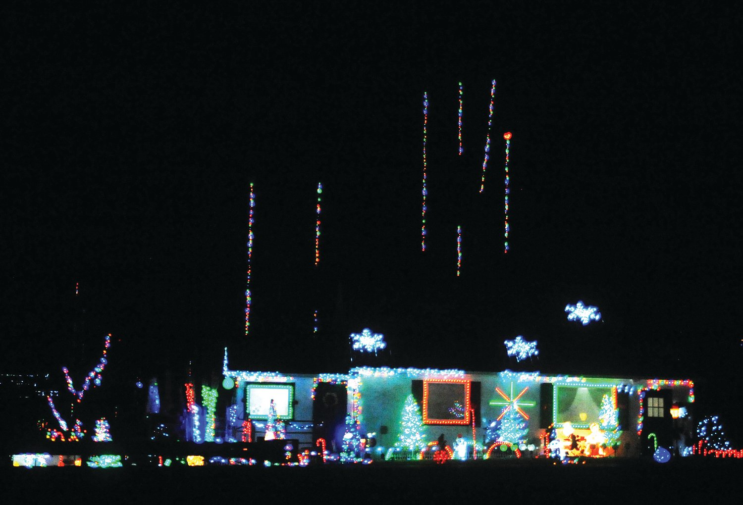 The Johnson family carries out their yearly tradition of bringing joy to the community by decorating their yard for with festive lights. The straight lines of lights were shot onto the treetops with a variety of methods, such as a potato gun or a drone. This year they used an arborist slingshot.