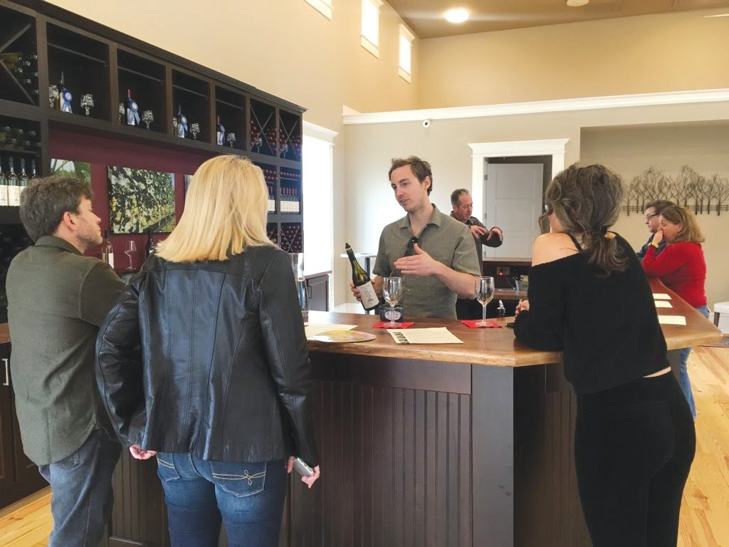Erik Mitran (center) and Beau Hall (background) do pours during a tasting at FireClay Cellars.