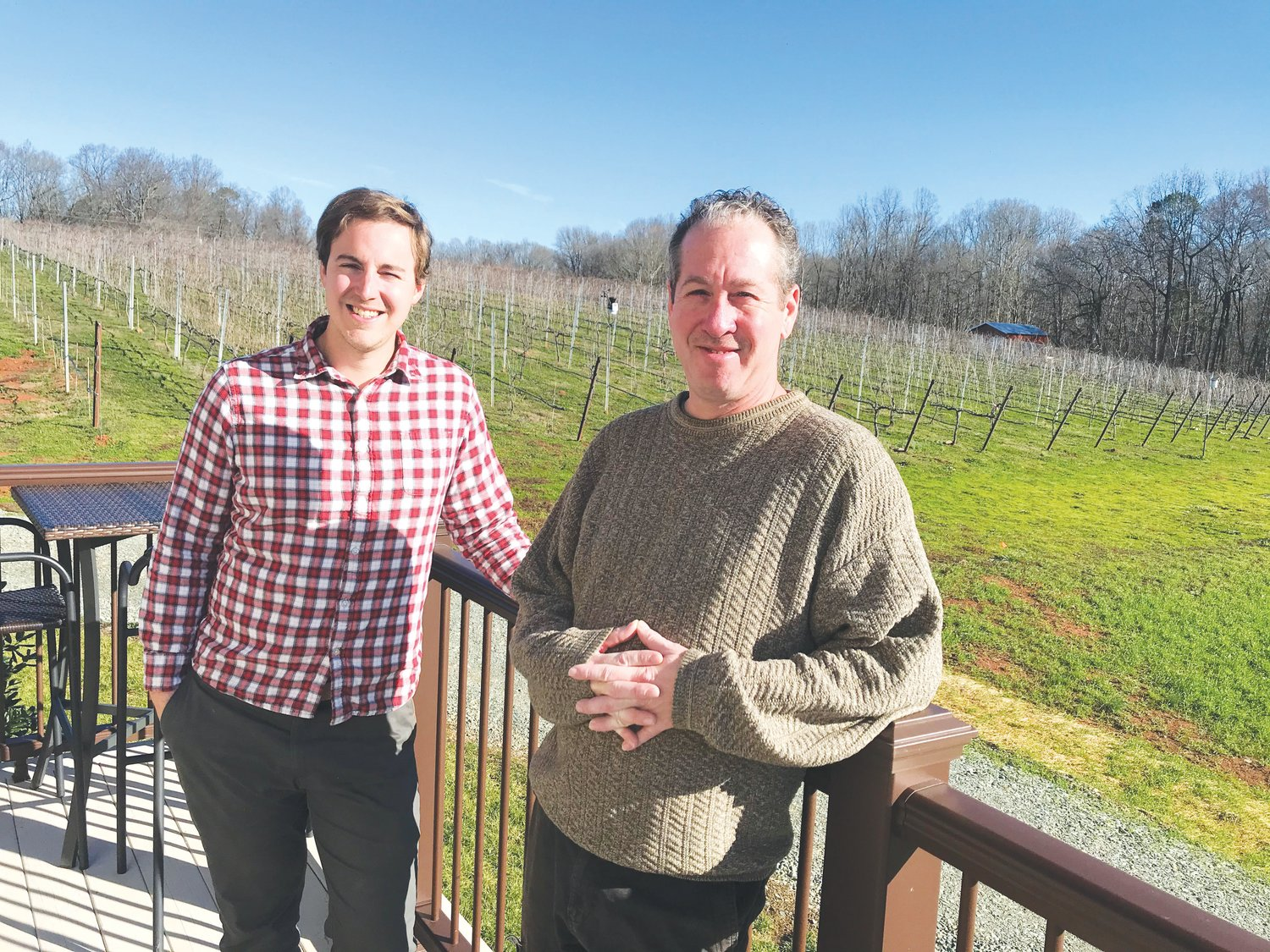 Erik Mitran (left) and Beau Hall pose on a deck overlooking FireClay Cellars' vineyard outside the tasting room there. The vineyard will soon see new growth from 1,200 new vines to be planted this spring.