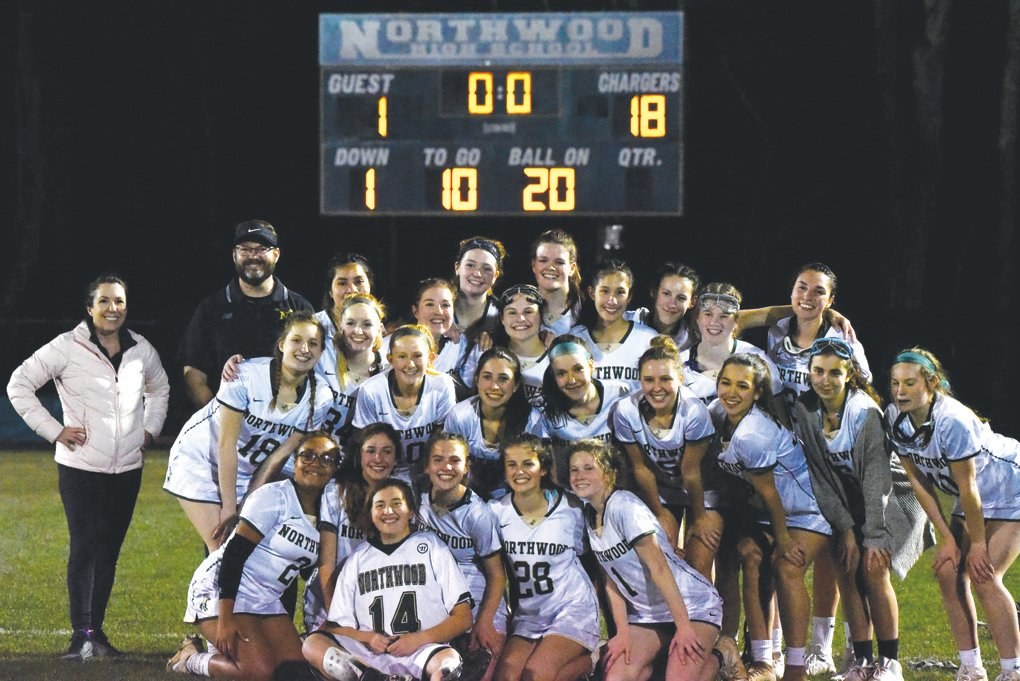 Goalie Madi Horrell (14), head coach Larry Fritsche (top, second from left) and the rest of the Northwood women's lacrosse team celebrate after winning their first ever game on March 4, at home versus Union Pines.