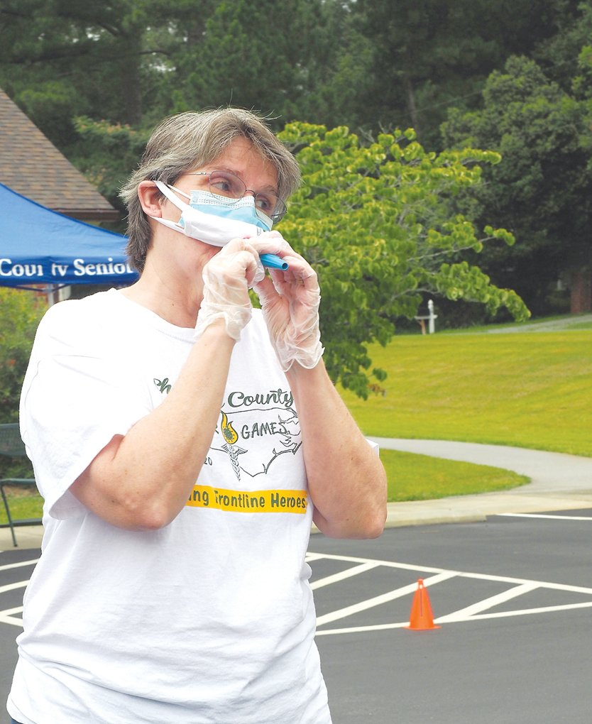 Patricia Cadle fires up the crowd with a kazoo at the Chatham County Senior Games drive-by ceremony on July 30.