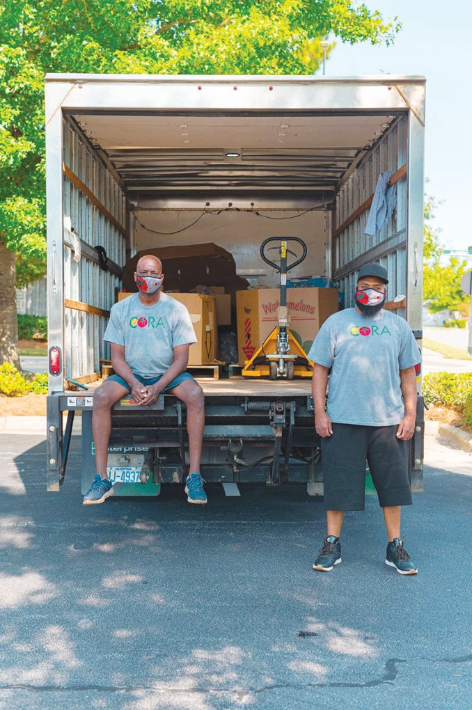 Reggie Blue (left) and Travis Viera pose for a shot with the CORA donation truck.