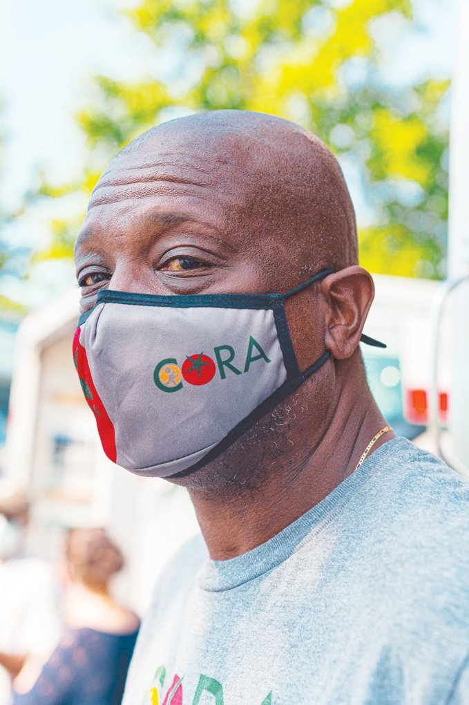 Reggie Blue pauses for a portrait to display his custom CORA face mask, a stylish addition to a wonderful cause.