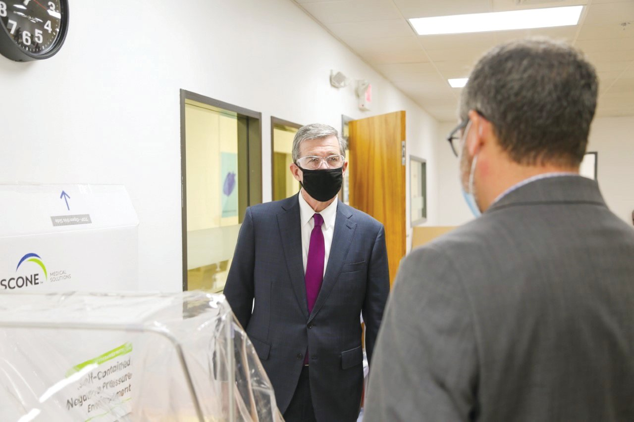 Gov. Roy Cooper speaks with executives from Pittsboro industry Gilero during a visit there Thursday. Gilero is one of the state's leading producers of PPE (personal protective equipment).