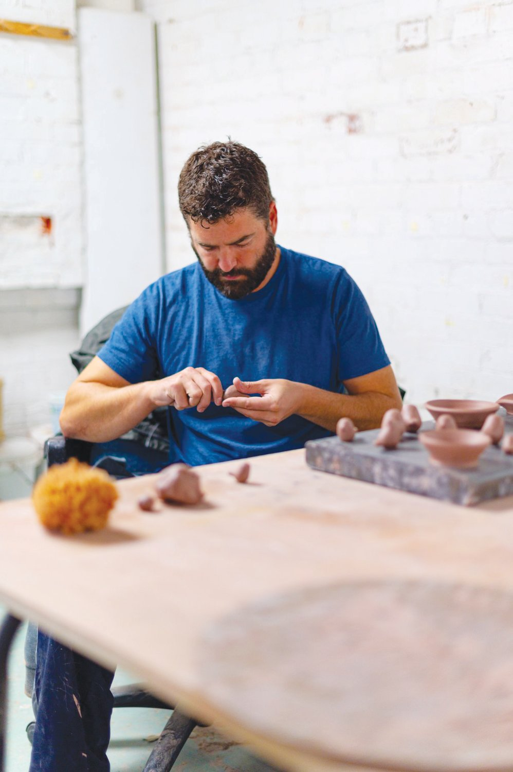 Spoon making a clay bird — a process he finds cathartic — in his Siler City Arts Incubator studio space.