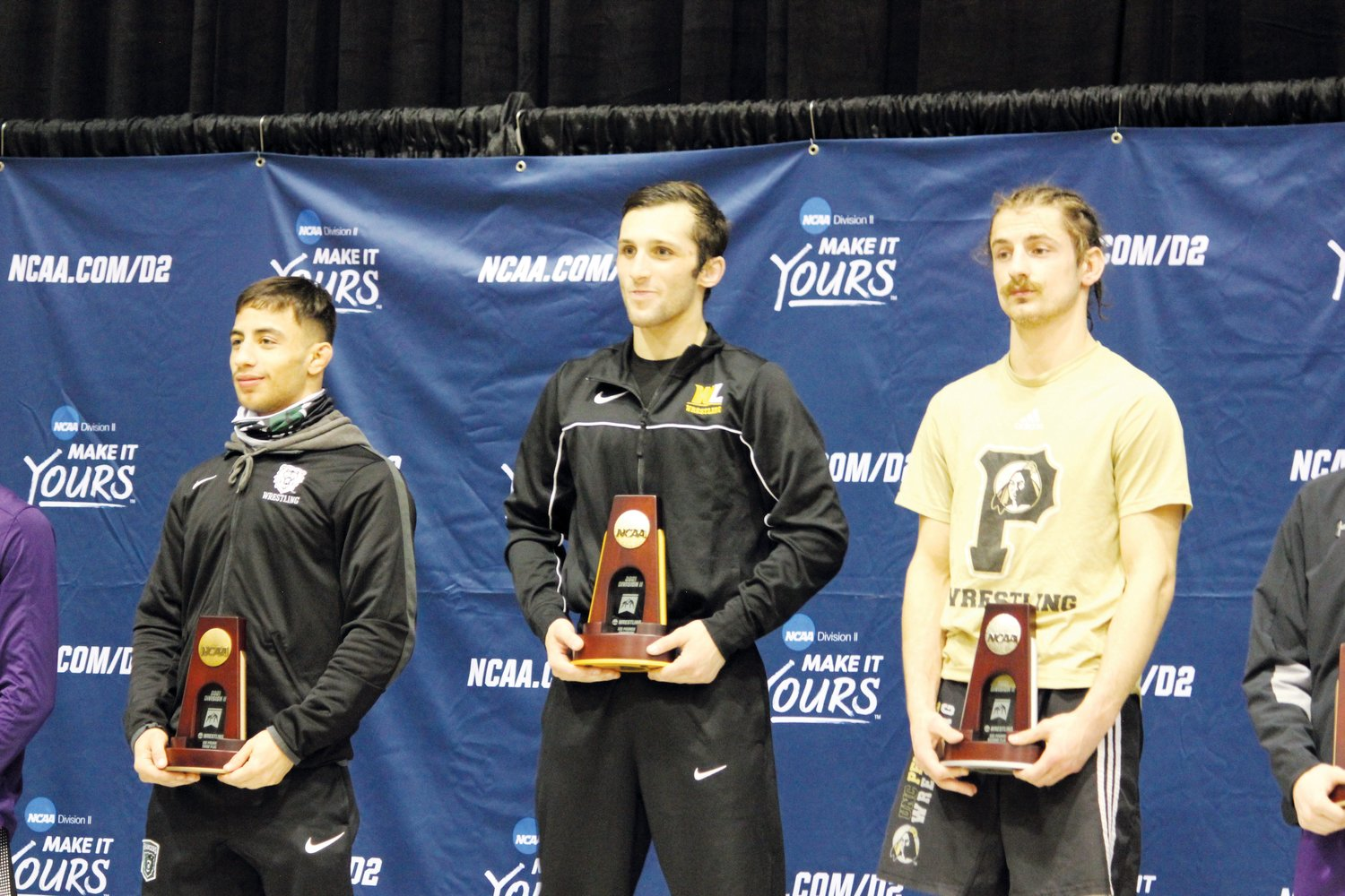 UNC Pembroke senior, and former Chatham Central wrestler, Nick Daggett (right) holds his runner-up trophy at the podium during the NCAA Division II Wrestling Championships in St. Louis over the weekend. Daggett lost by major decision, 12-2, to West Liberty's Cody Laya (center).