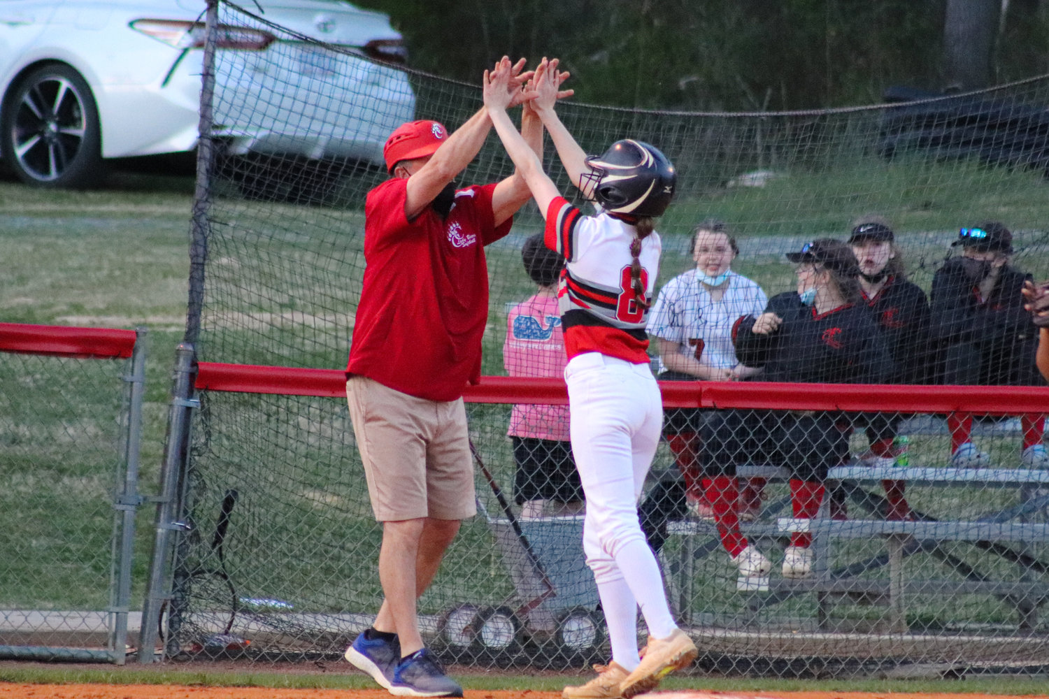 Chatham Central junior Gracie Gaines (8) celebrates with her head coach, Jerry Polston, at third base after a 2-RBI triple in the second inning of her team's 12-0 win over North Rowan on March 30.