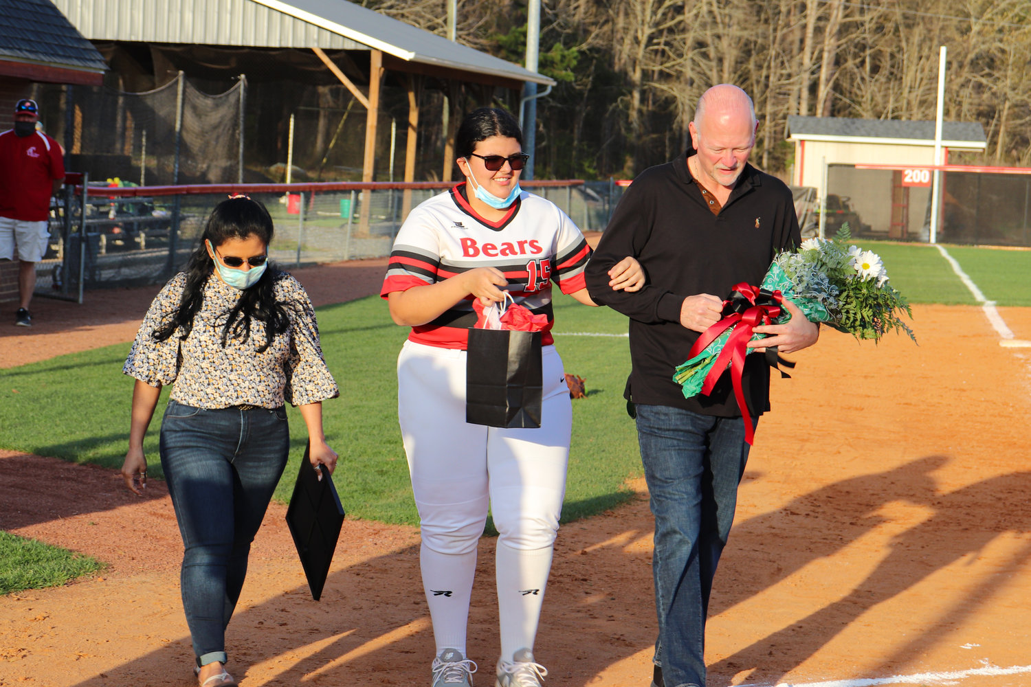 Chatham Central senior Katie Sanders (15) walks to home plate with her parents during the senior night festivities before the Bears' 12-0 win over North Rowan on March 30.