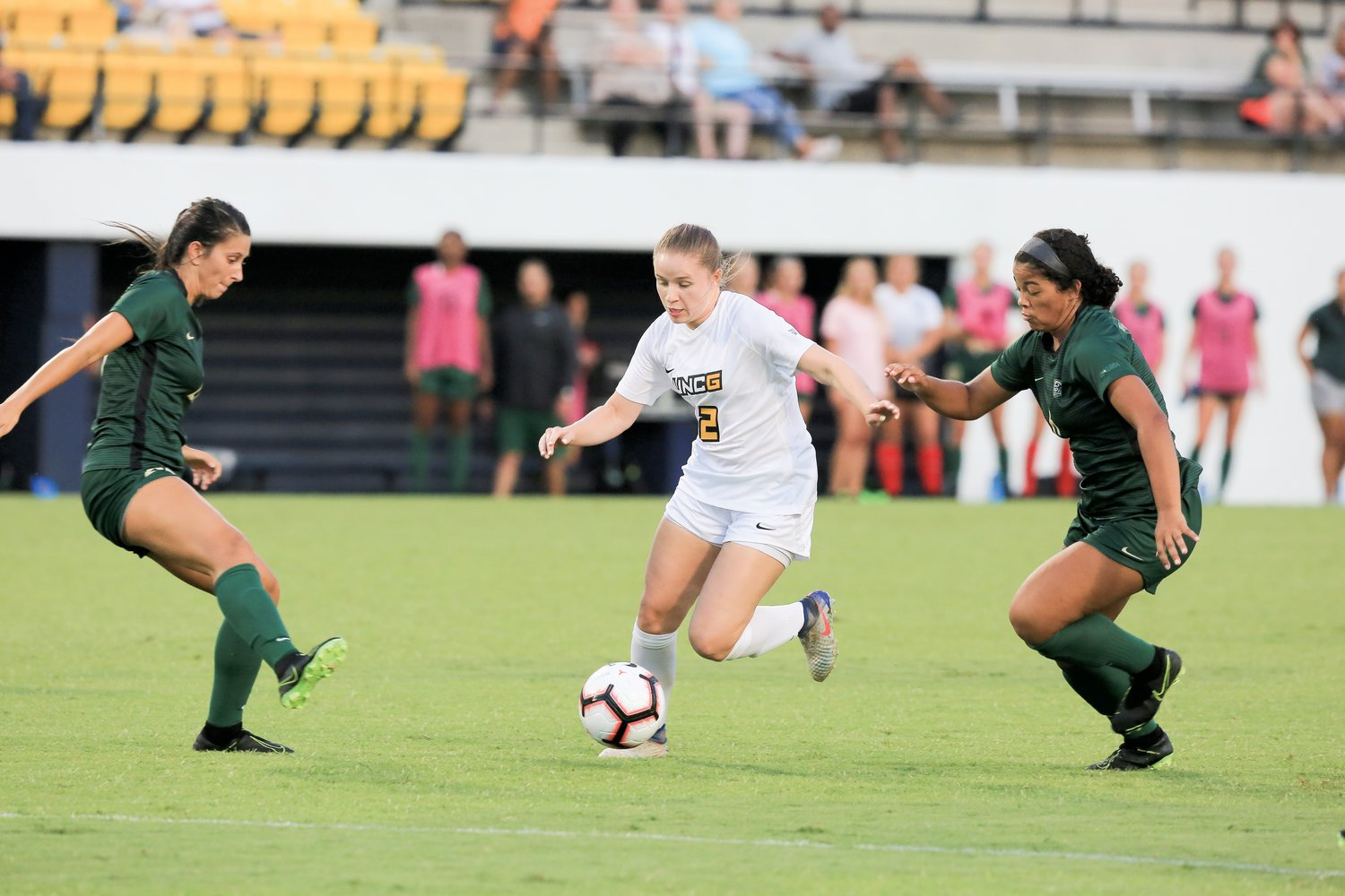 UNCG's Isabel Pearce (2) dribbles through a pair of defenders in an exhibition game against the Charlotte 49ers on August 11, 2019. Pearce is the NCHSAA women's soccer leader in career goals scored (226).