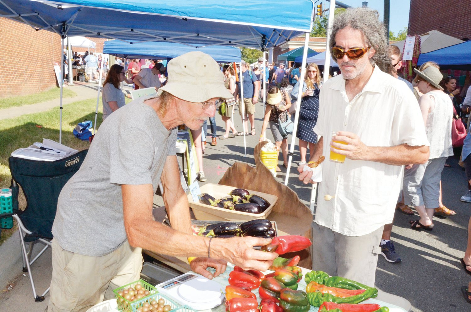 Doug Jones, pepper farmer, gives David DelVecchio a brief tour of his produce available at Pepperfest last Sunday. DelVecchio said that Jones is the reason for the festival; he's been breeding peppers for years, and started with a tasting area on Lorax Lane.