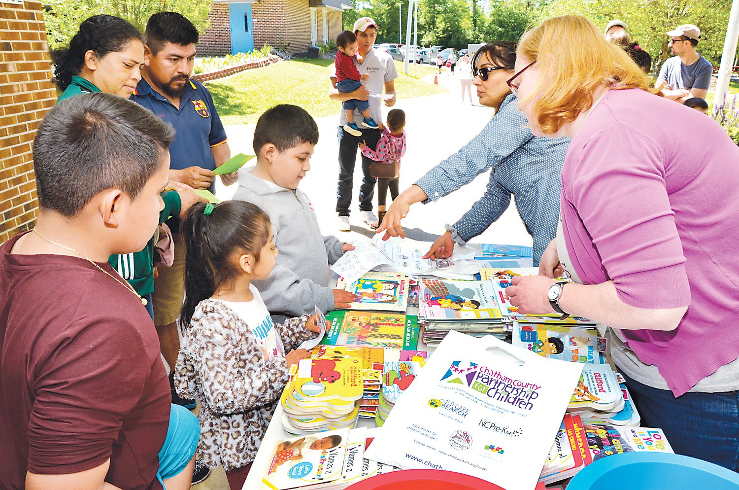 Belarmino Vicente and his family go through the registration table for The Day of the Books at Siler City Elementary School back in 2019. Each child receives a free bilingual book here before going into the building for more books and fun.