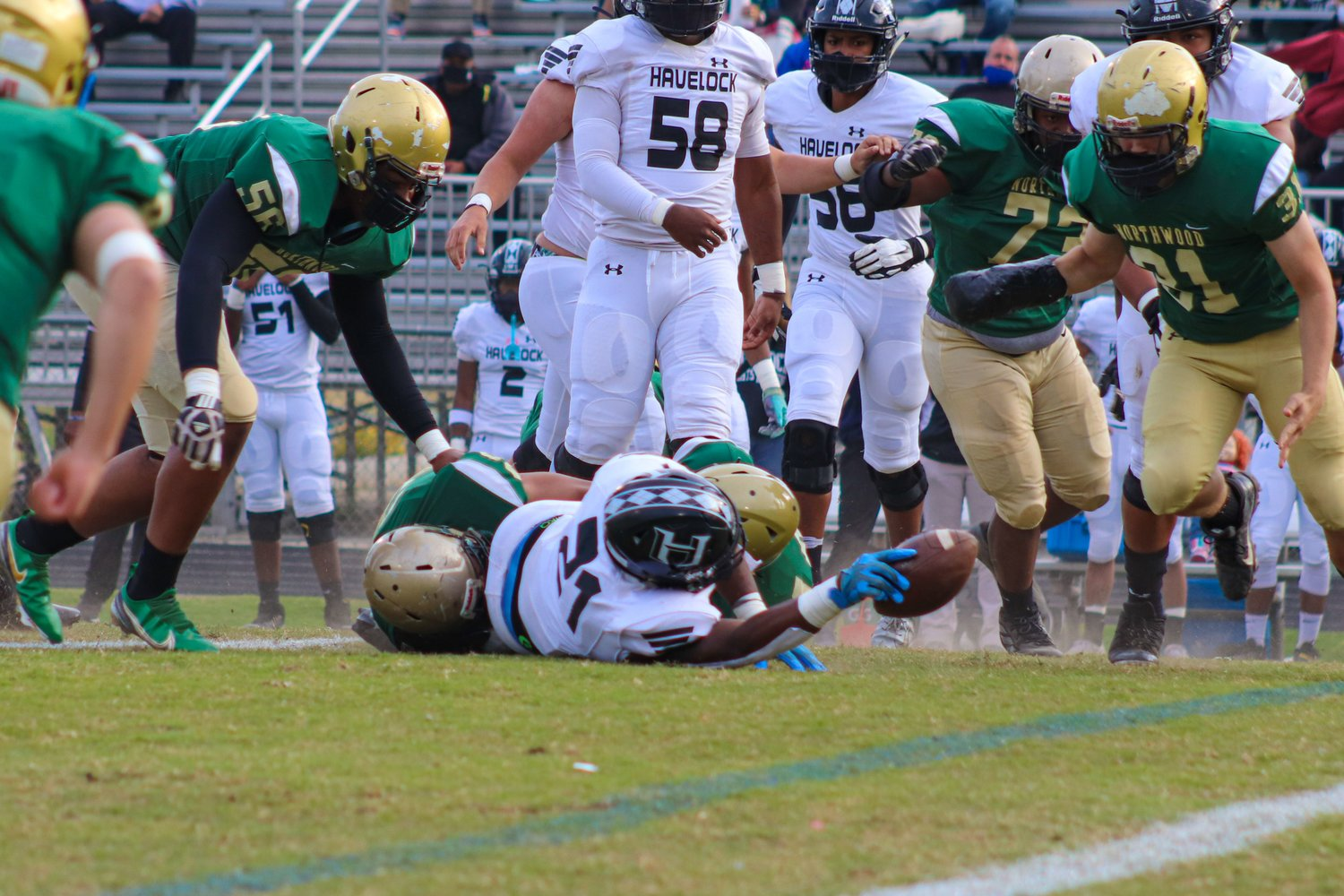 Havelock senior running back Kamarro Edmonds (21) stretches for a first down as he's brought to the ground by a pair of Northwood defenders in his team's 32-7 win over the Chargers last Friday. Edmonds is a 2021 commit to North Carolina.
