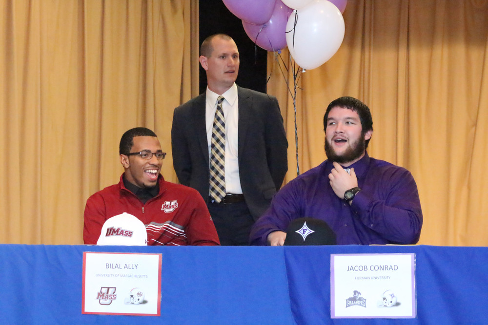 Clay signees  Clay High running back Bilal Ally, left, smiles with offensive lineman Jacob Conrad as coach Joshua Hoekstra introduces the pair at the February 3 National Signing Day ceremonies at Clay High School. Clay signed seven scholarships with Ally heading to the University of Massachusetts and Conrad going to Furman University.